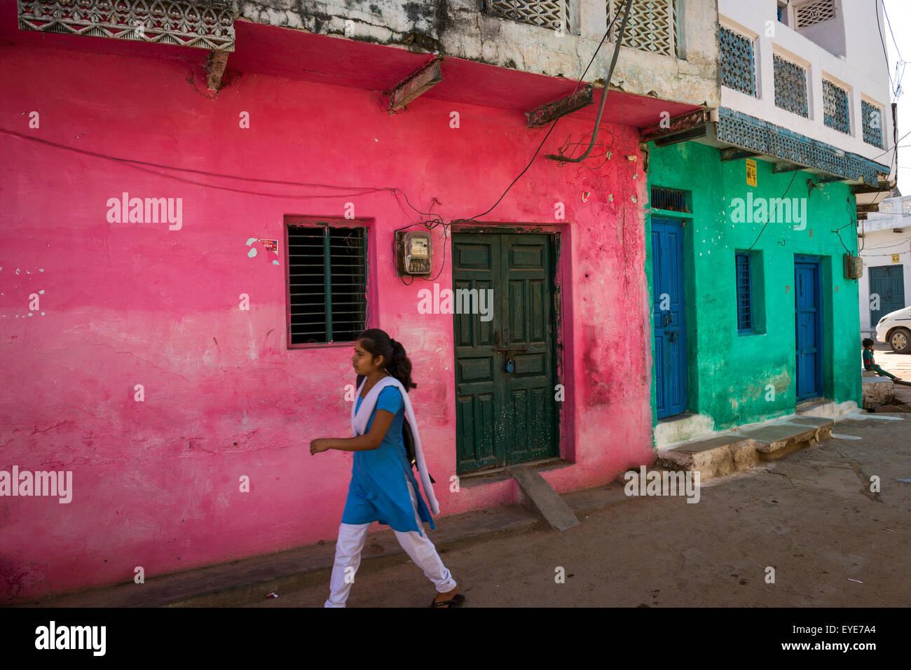 Junge indische Frau zu Fuß vorbei an bunten Häusern im alten Dorf von Khajuraho, Madhya Pradesh, Indien Stockbild