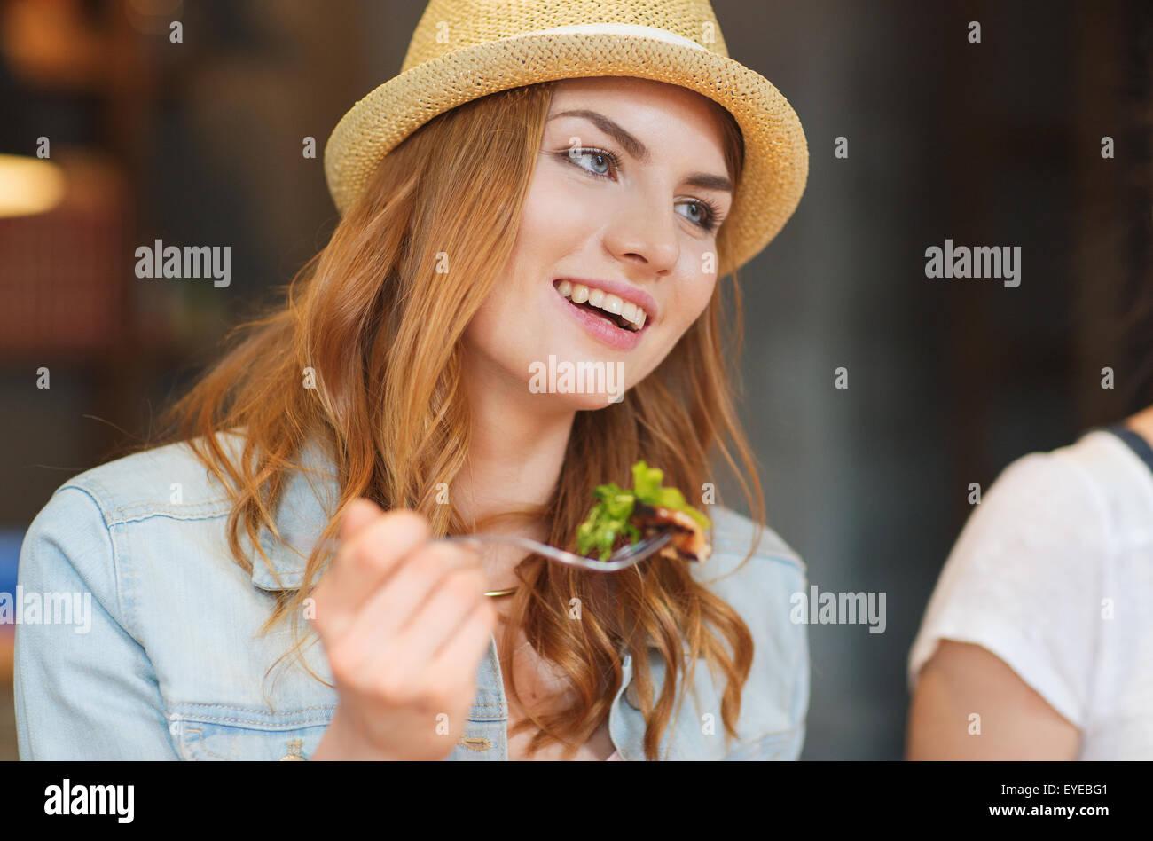 glückliche junge Frau essen Salat an Bar oder Kneipe Stockbild
