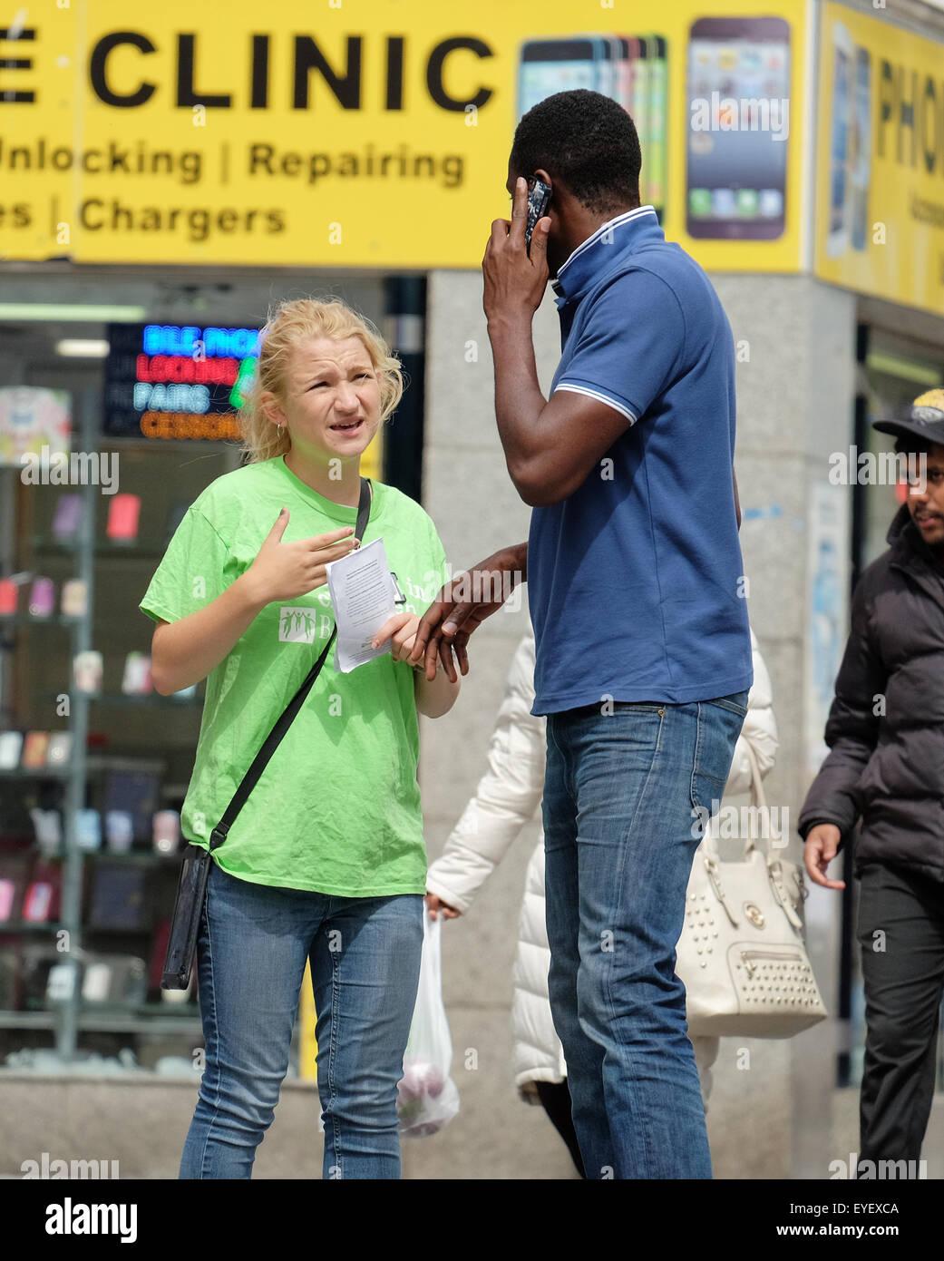 Ein Charity-Chugger stoppen einen Fußgänger auf der Straße in Southampton Stockbild