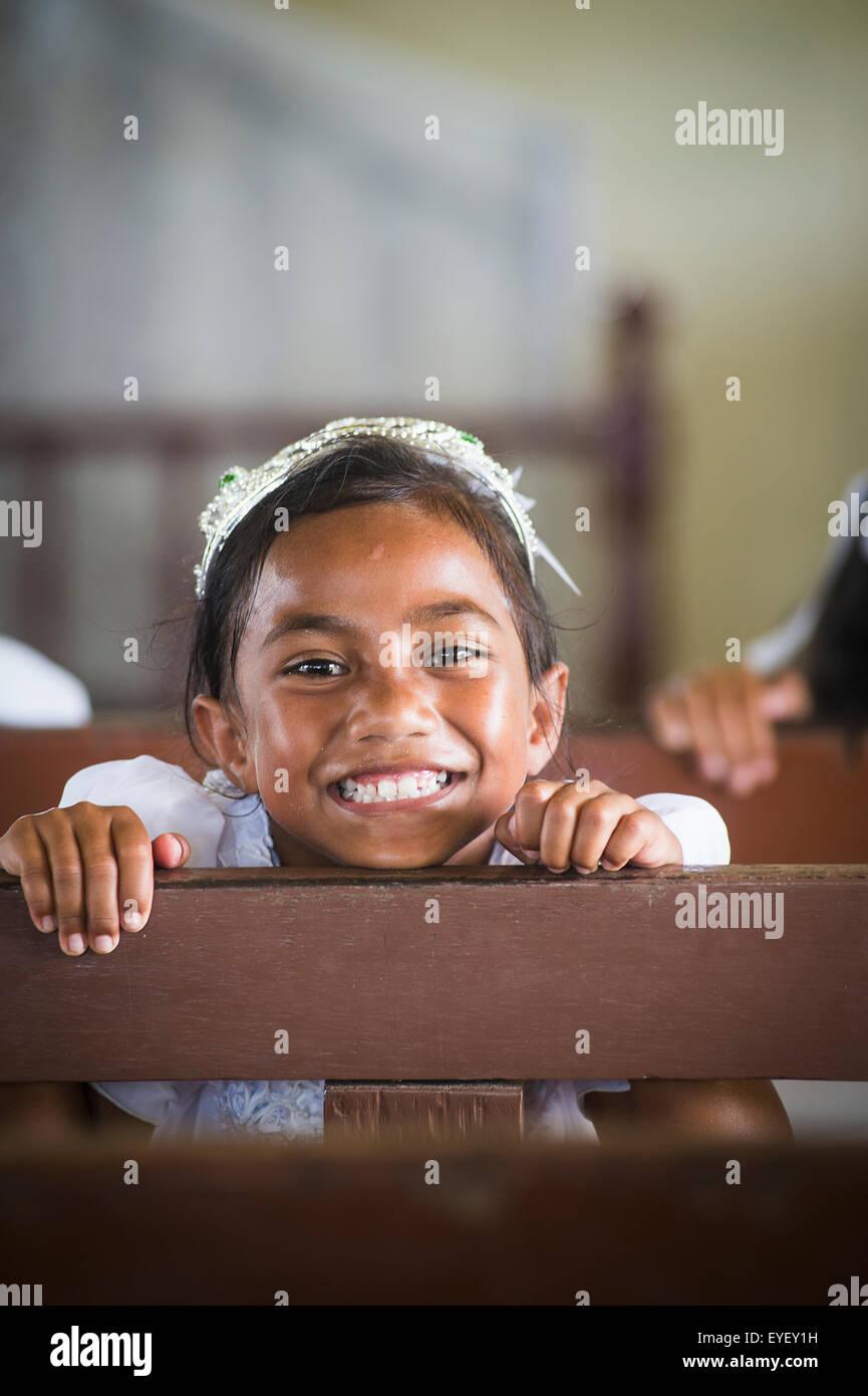 Junges Mädchen auf Holzbank in der Kirche auf Hapai Insel; Tonga Stockbild