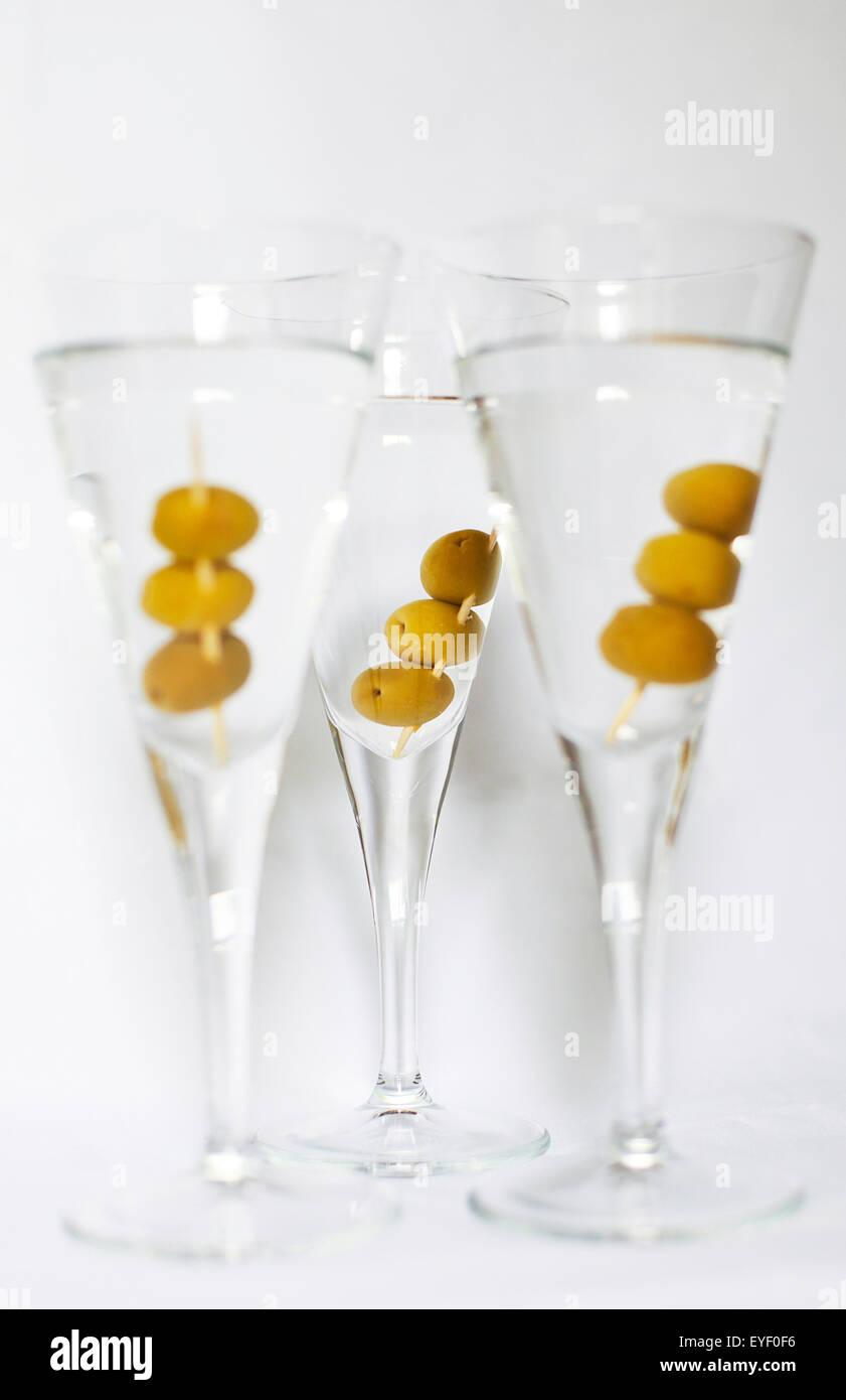 Drei Martini-Cocktails mit Oliven vor einem weißen Hintergrund Stockfoto