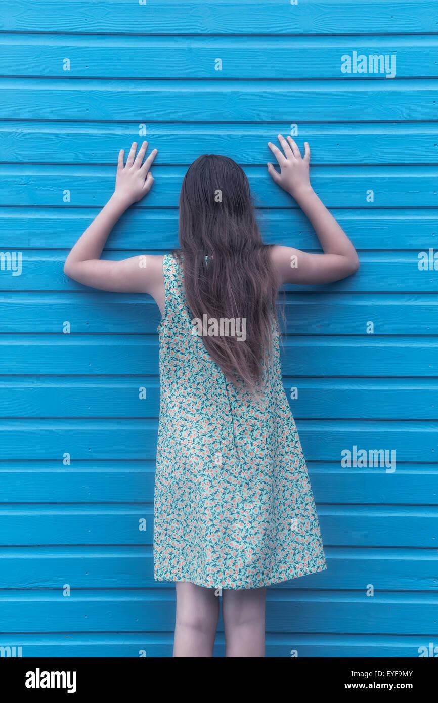 eine Mädchen mit einem geblümten Kleid ist an einer Holzwand gelehnt. Stockbild