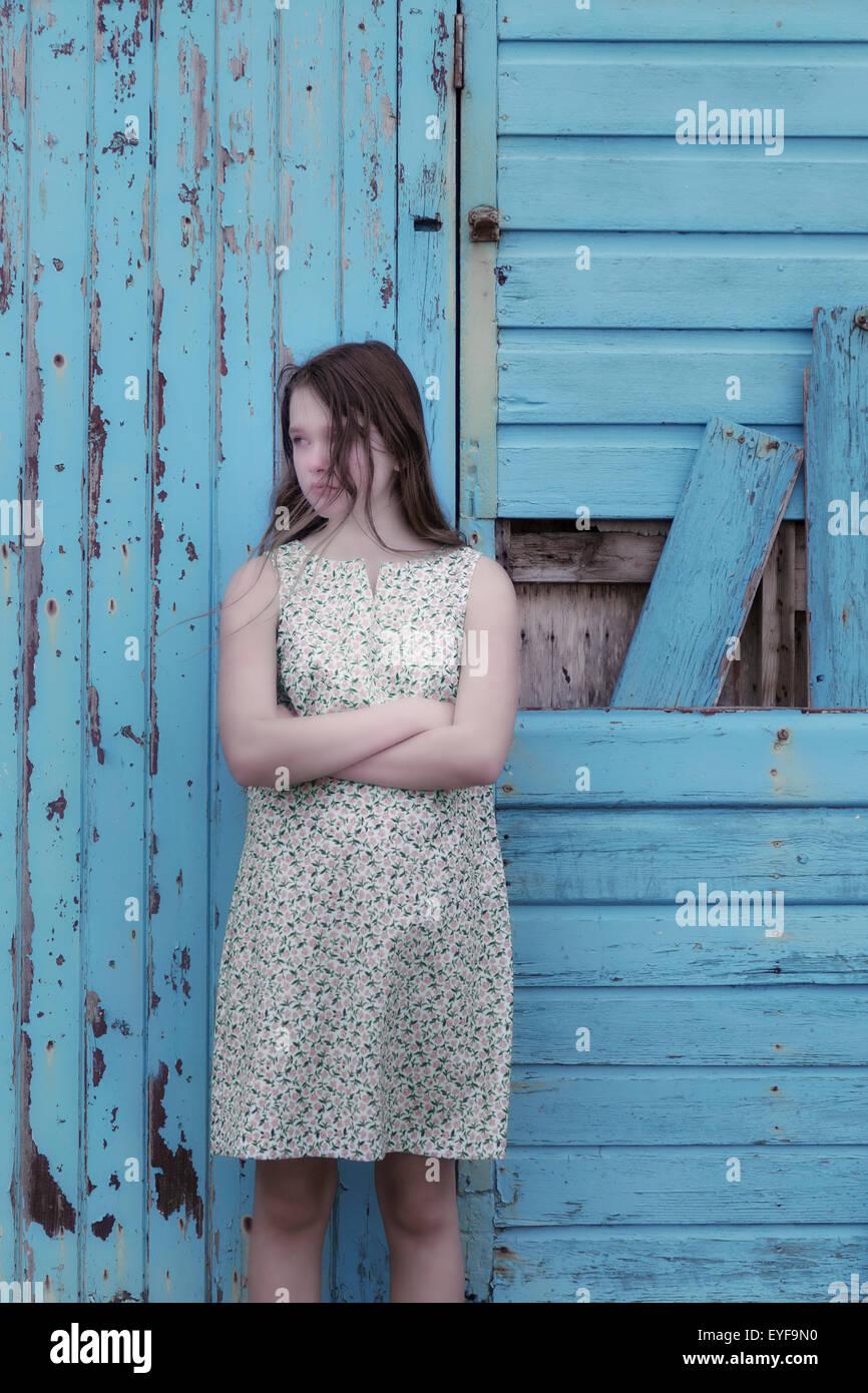 eine Mädchen in einem geblümten Kleid steht vor einer blauen Wand aus Holz Stockbild