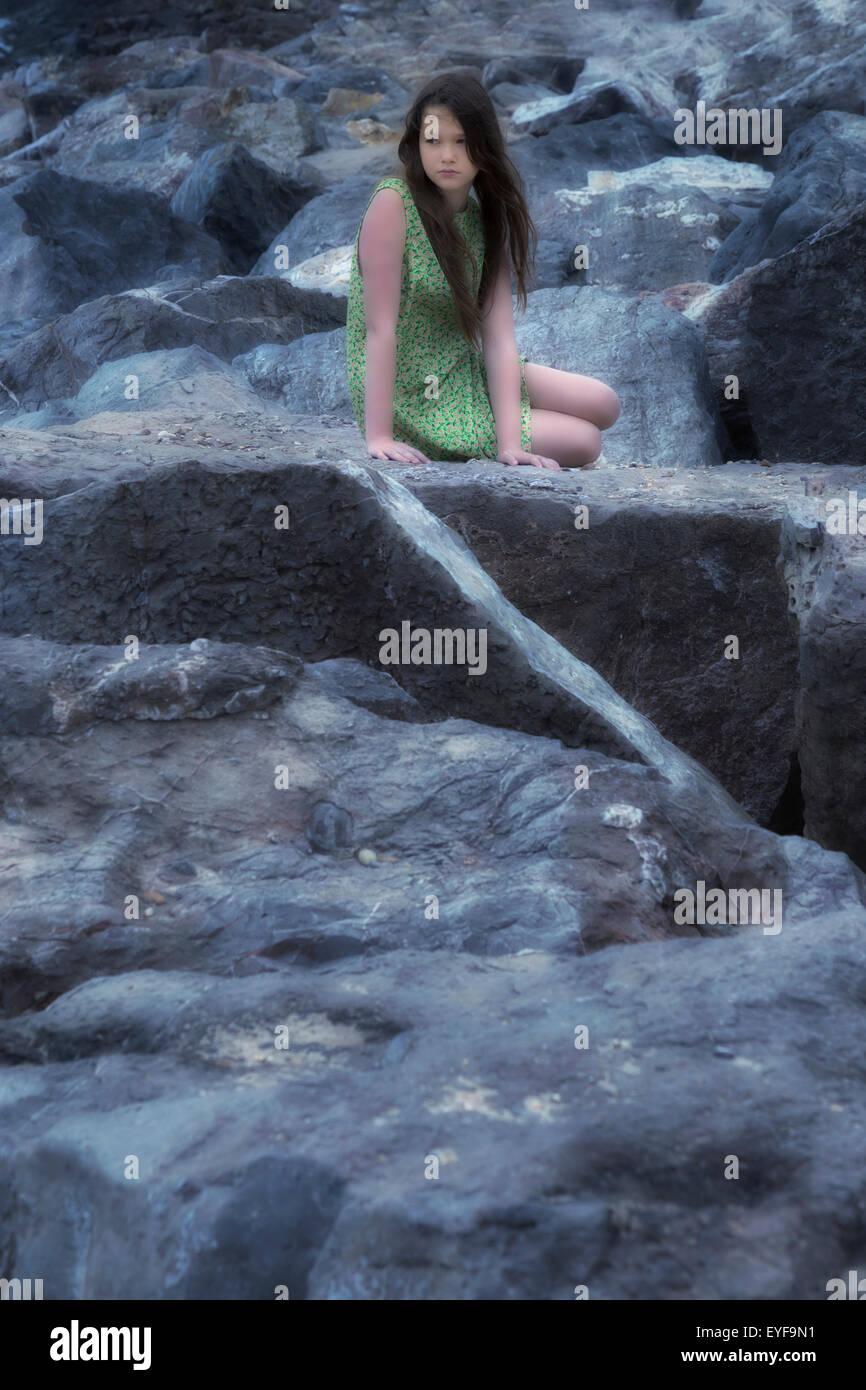 eine Mädchen in einem geblümten Kleid sitzt auf Steinen Stockbild