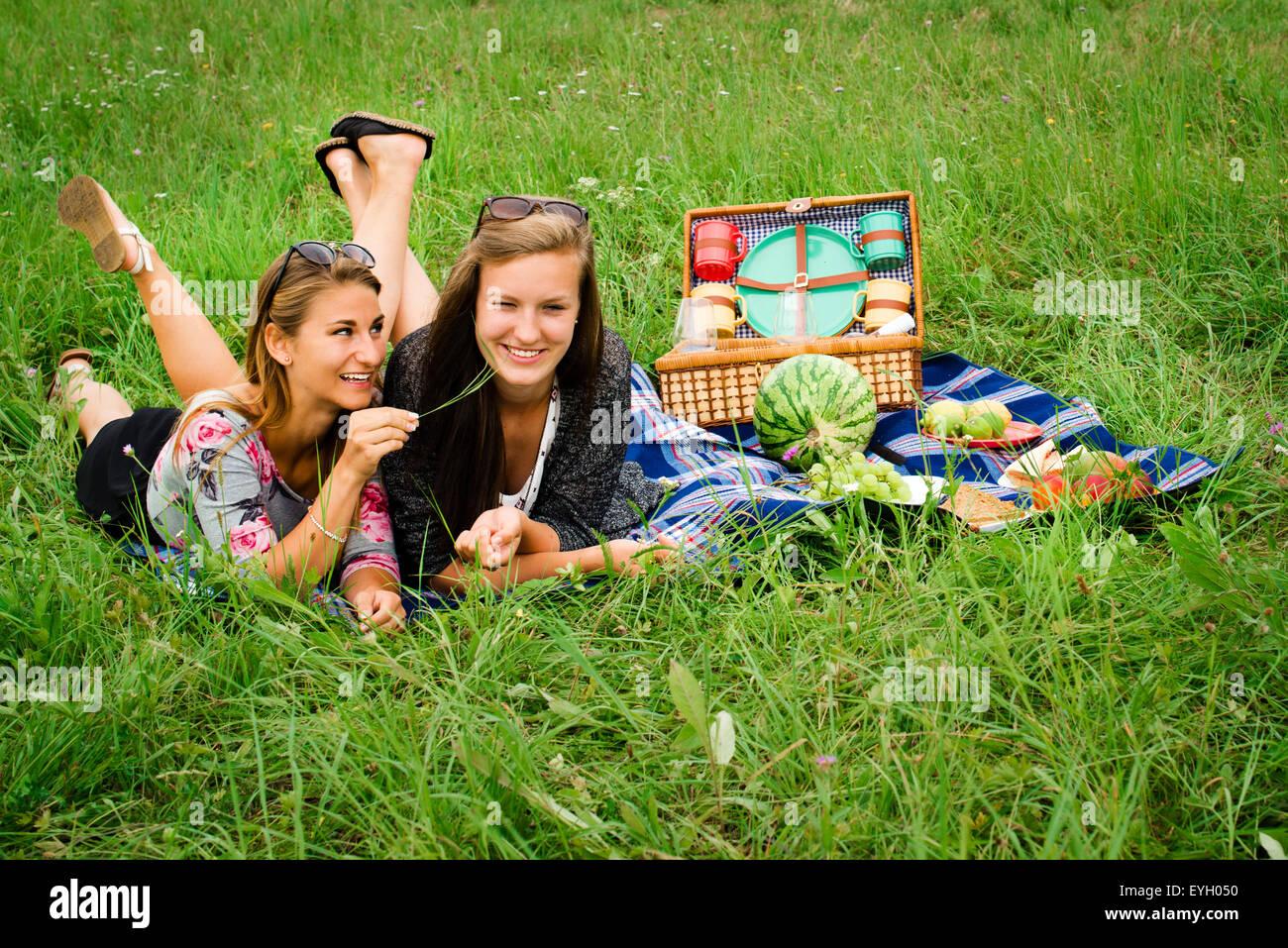 beste freunde zwei attraktive junge m dchen haben ein picknick bekleidet l ssig auf dem rasen. Black Bedroom Furniture Sets. Home Design Ideas