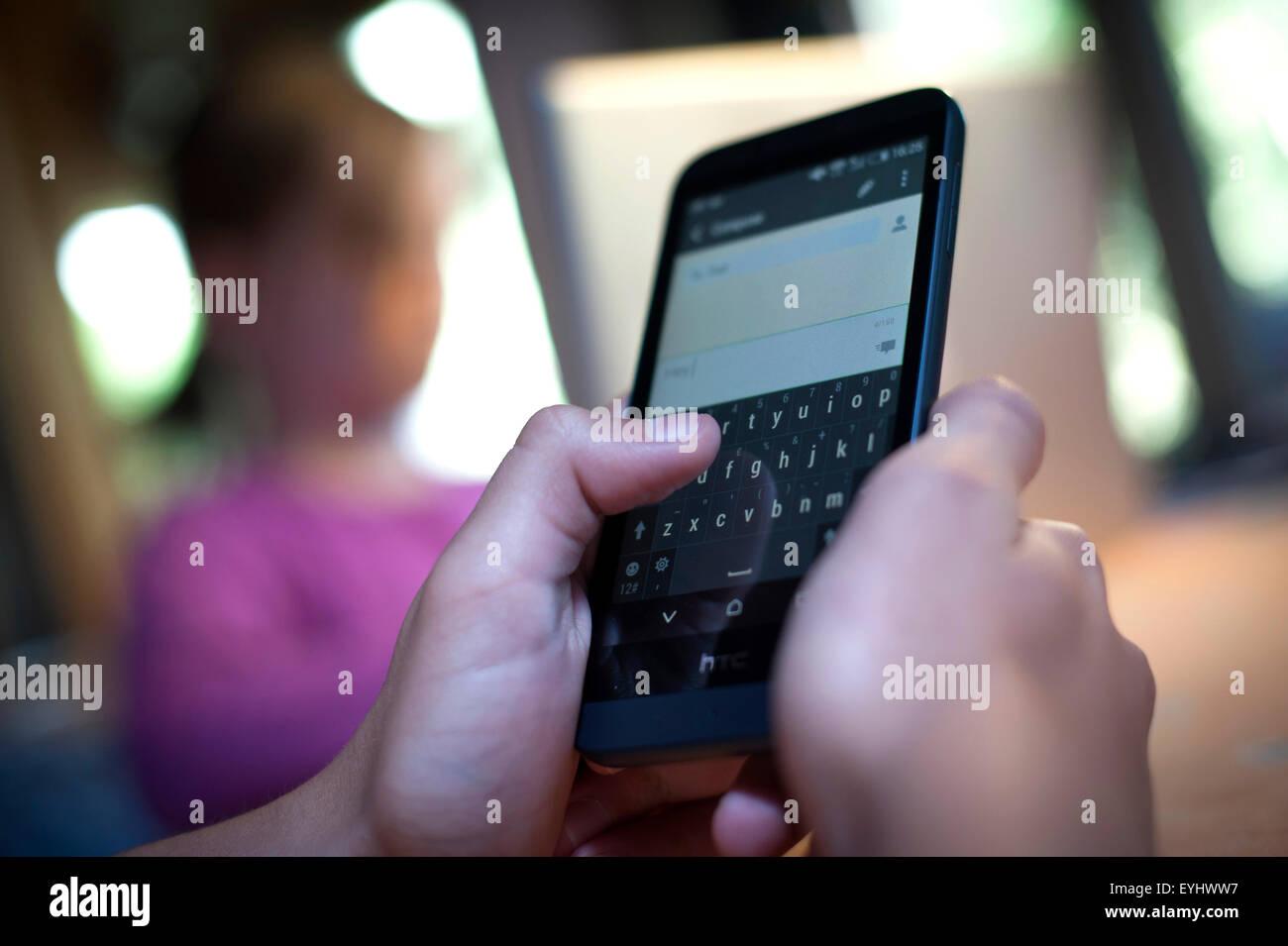 Teenager-SMS auf einem Smartphone zu Hause. Stockbild