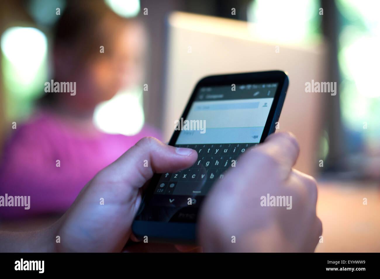 Teenager mit einem Smartphone zu Hause. Stockbild