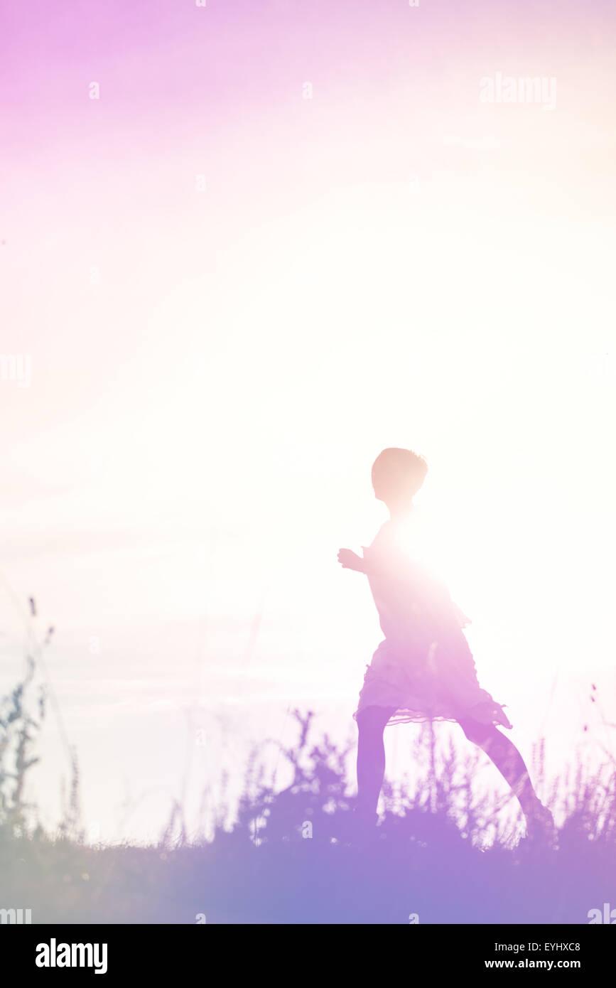 Frau läuft in die Freiheit durch Landschaft Feld, Flucht, Breakout Konzept, Silhouette der weiblichen Person, Stockbild