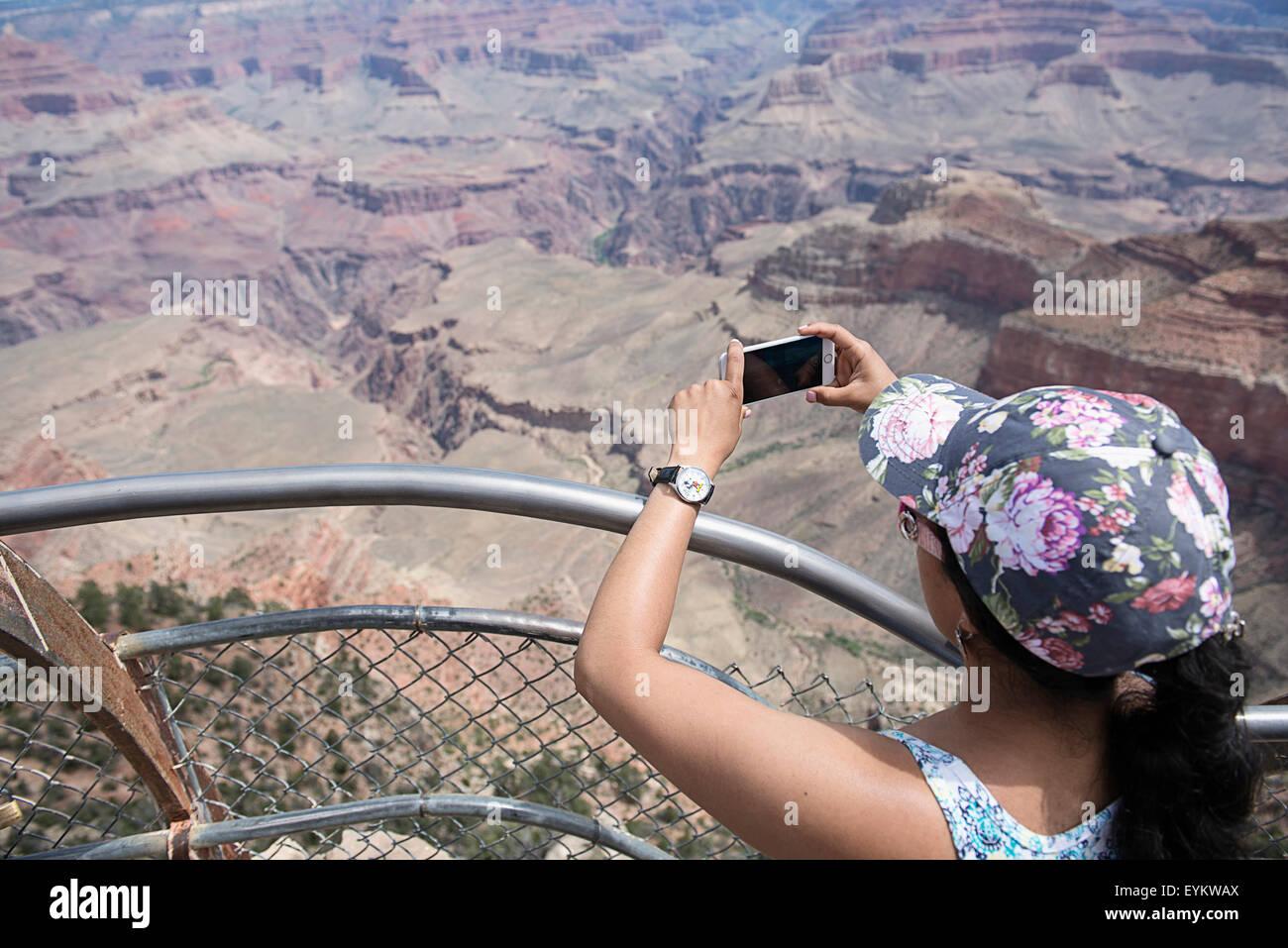 Eine Frau, die Fotos von der Grand Canyon auf ihrem Iphone. Stockbild