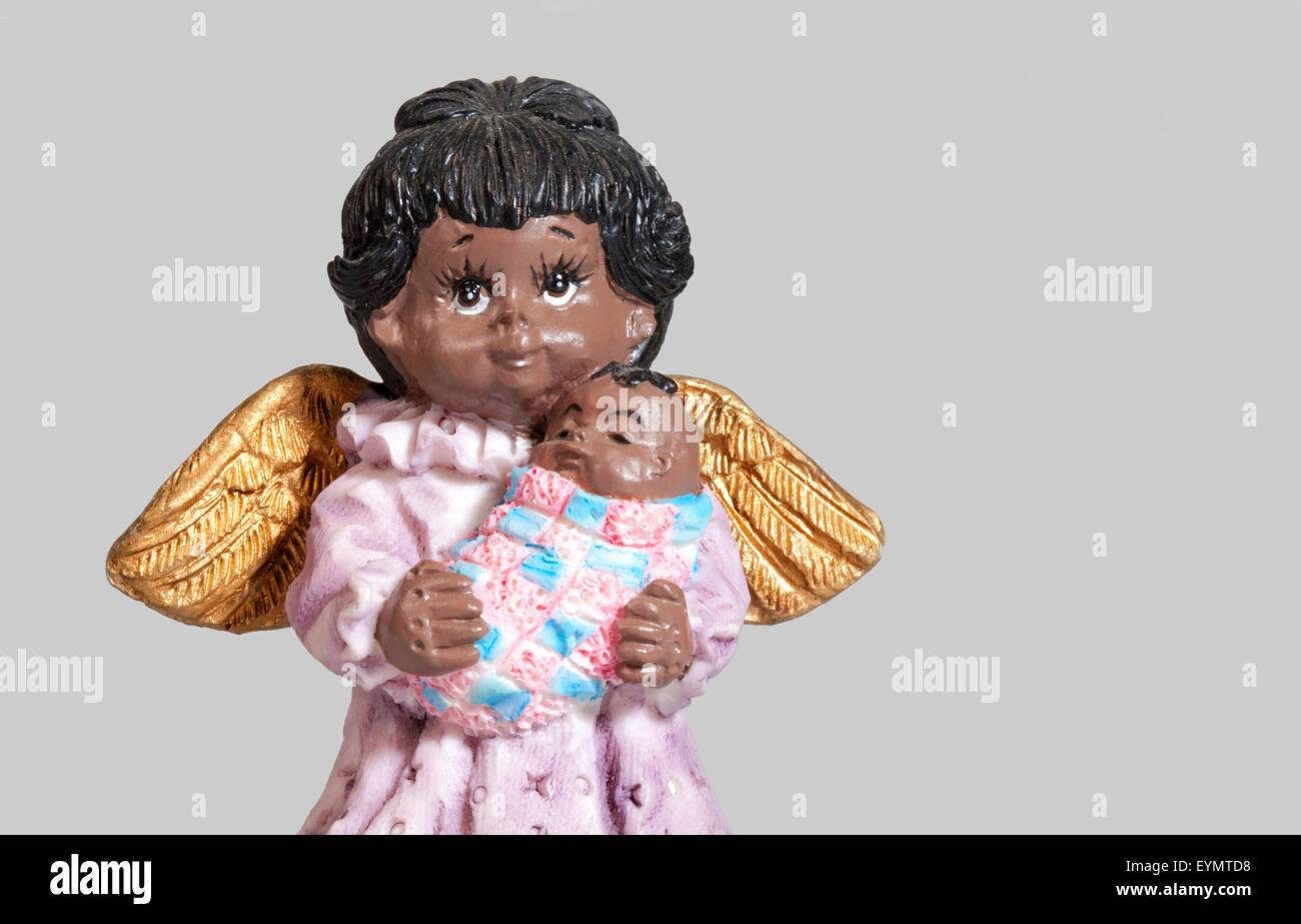 dunkel-enthäutete Weihnachtsengel mit einem Baby, Stockbild