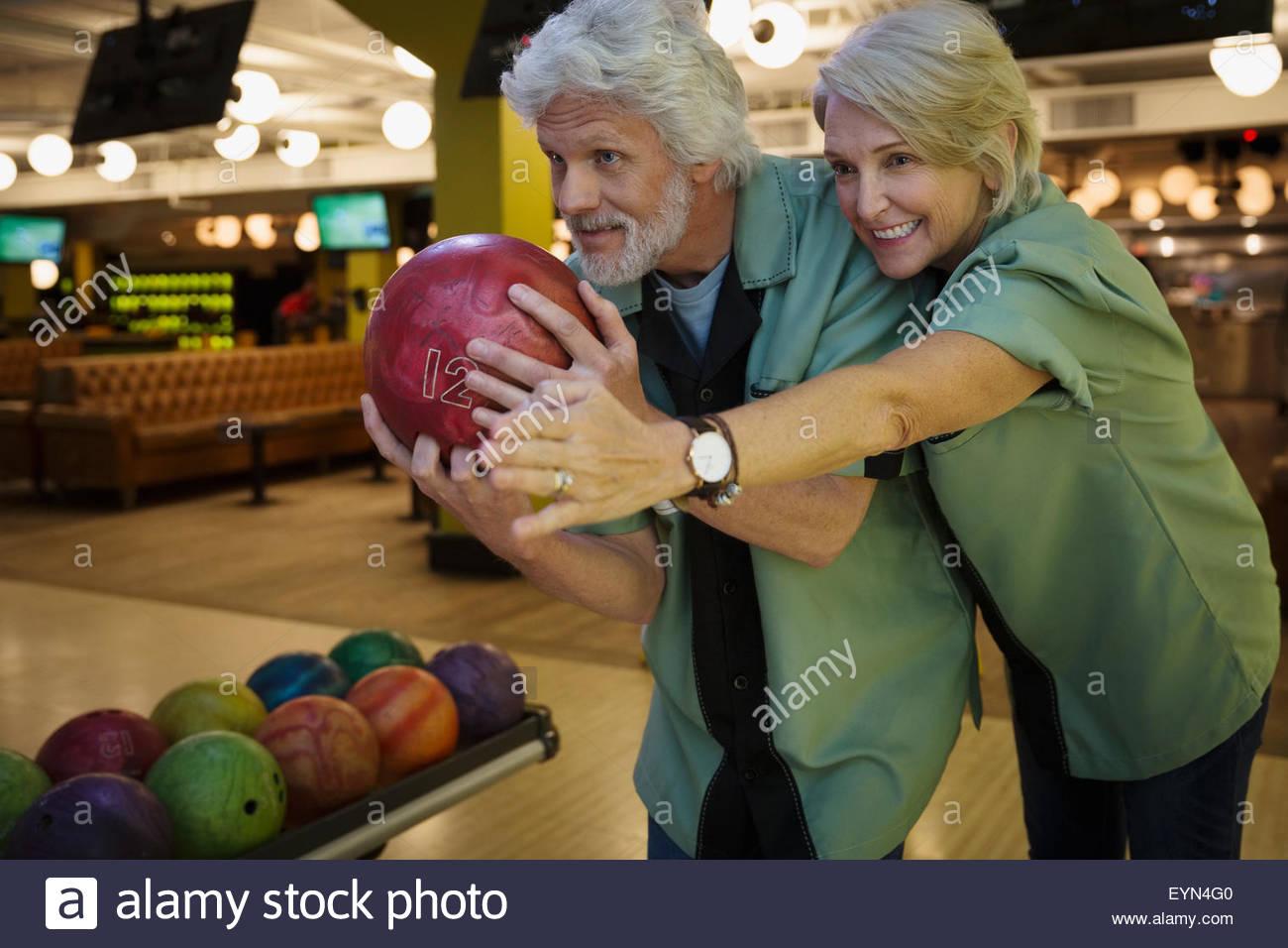 Ehefrau leitende Ehemann auf Kegelbahn Kegeln Stockbild