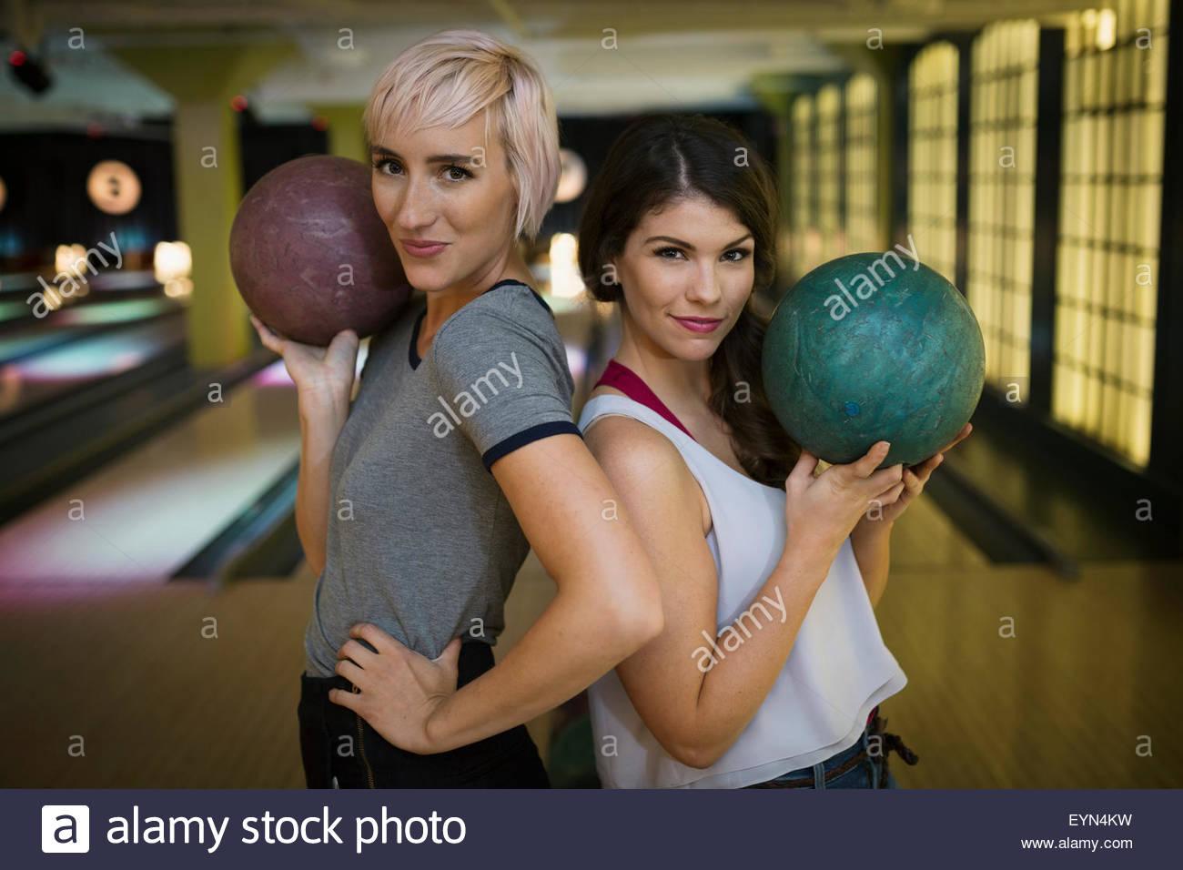 Porträt selbstbewusste junge Frauen halten Bowlingkugeln Stockbild