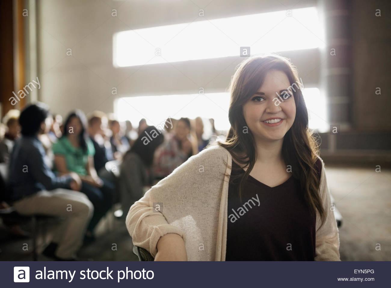 Porträt lächelnde Brünette Frau im Auditorium Publikum Stockbild