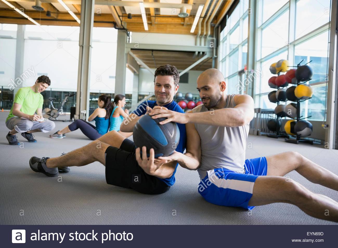 Männer Medizinball volle Wendung Rücken an Rücken Stockbild