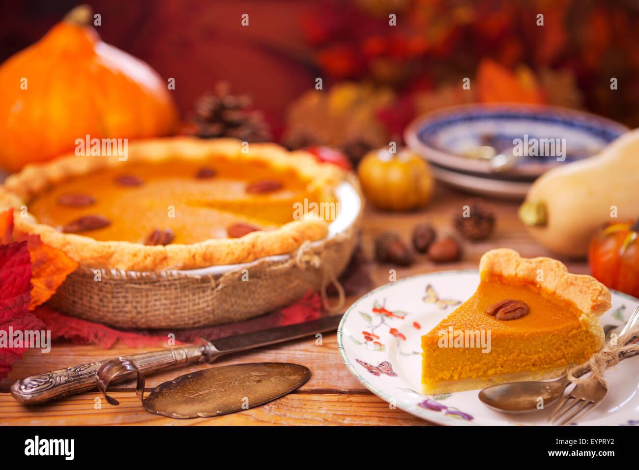 Hausgemachte Kürbis-Kuchen auf einem rustikalen Tisch mit herbstlichen Dekorationen. Stockfoto