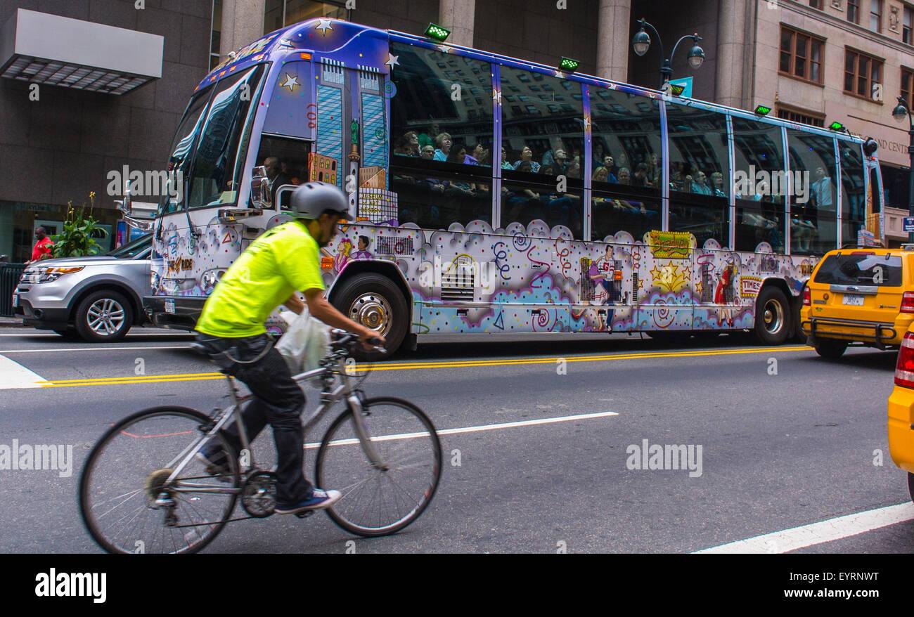 New York City, USA, Masse auf bunt geschmückten Touristenbus auf Street, Manhattan, Mann auf dem Fahrrad Stockbild