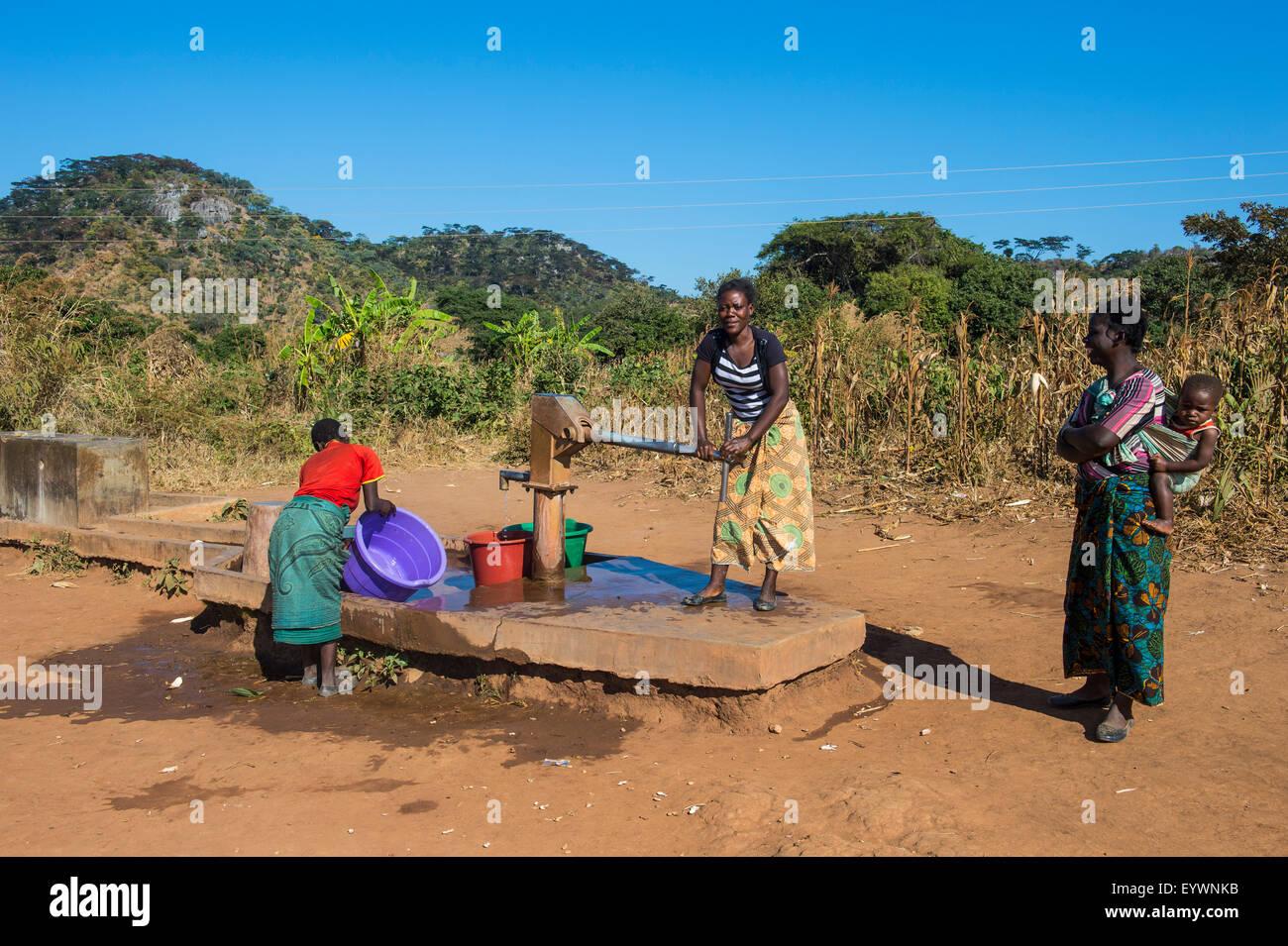 Einheimische Frauen an einem Wasser gut, Malawi, Afrika Stockbild