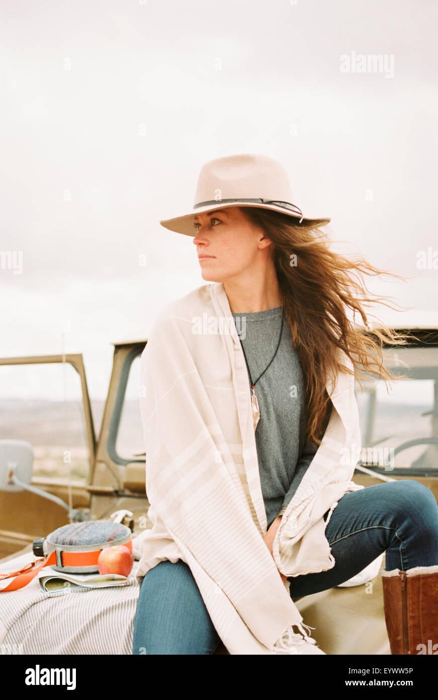 Frau trägt einen Hut sitzt auf der Vorderseite eines Jeeps auf der Suche um sie herum. Stockbild