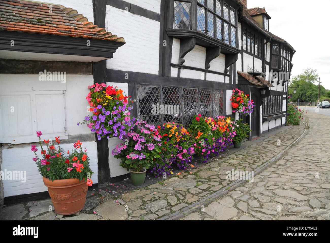Bunte Balkonkästen rund um Gitter Fenster des mittelalterlichen Weber Cottage in Biddenden, Kent, UK Stockbild