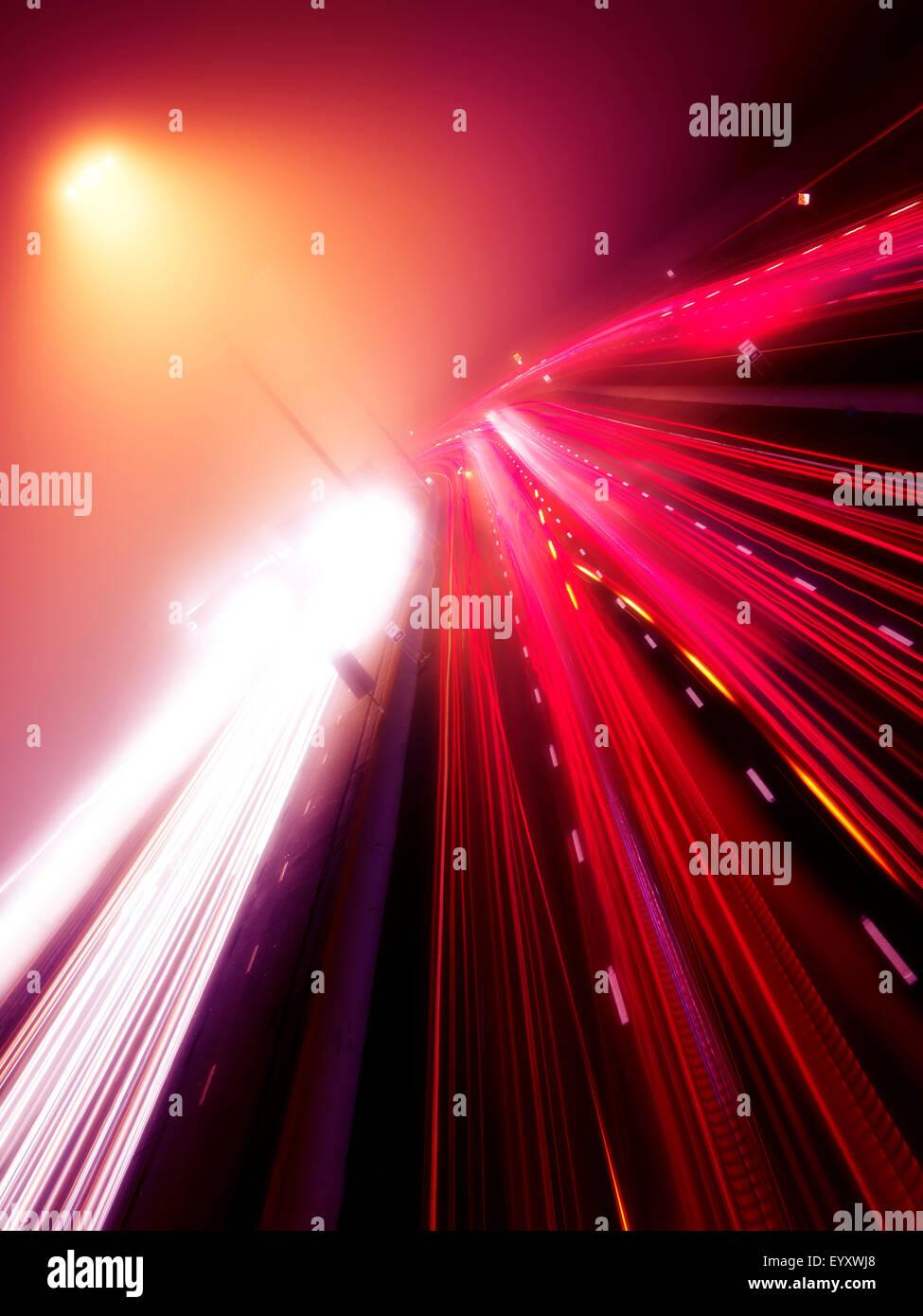 Bunte Lichtspuren der viel befahrenen Autobahnverkehr auf einer nebligen Nacht, Highway 401, Toronto, Ontario, Kanada. Stockbild
