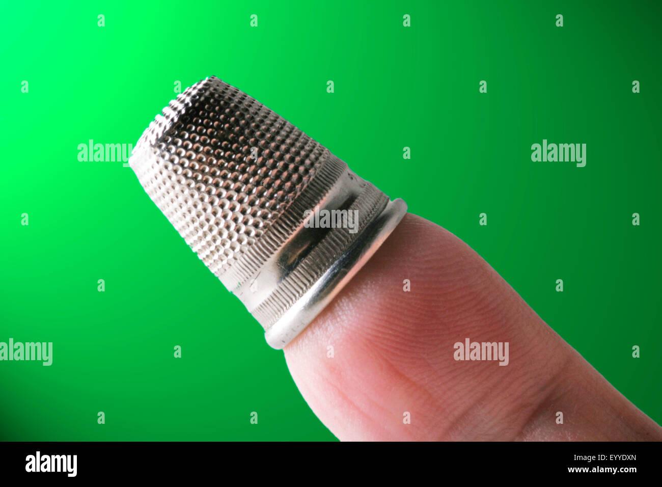 silbrig Fingerhut auf einen finger Stockbild