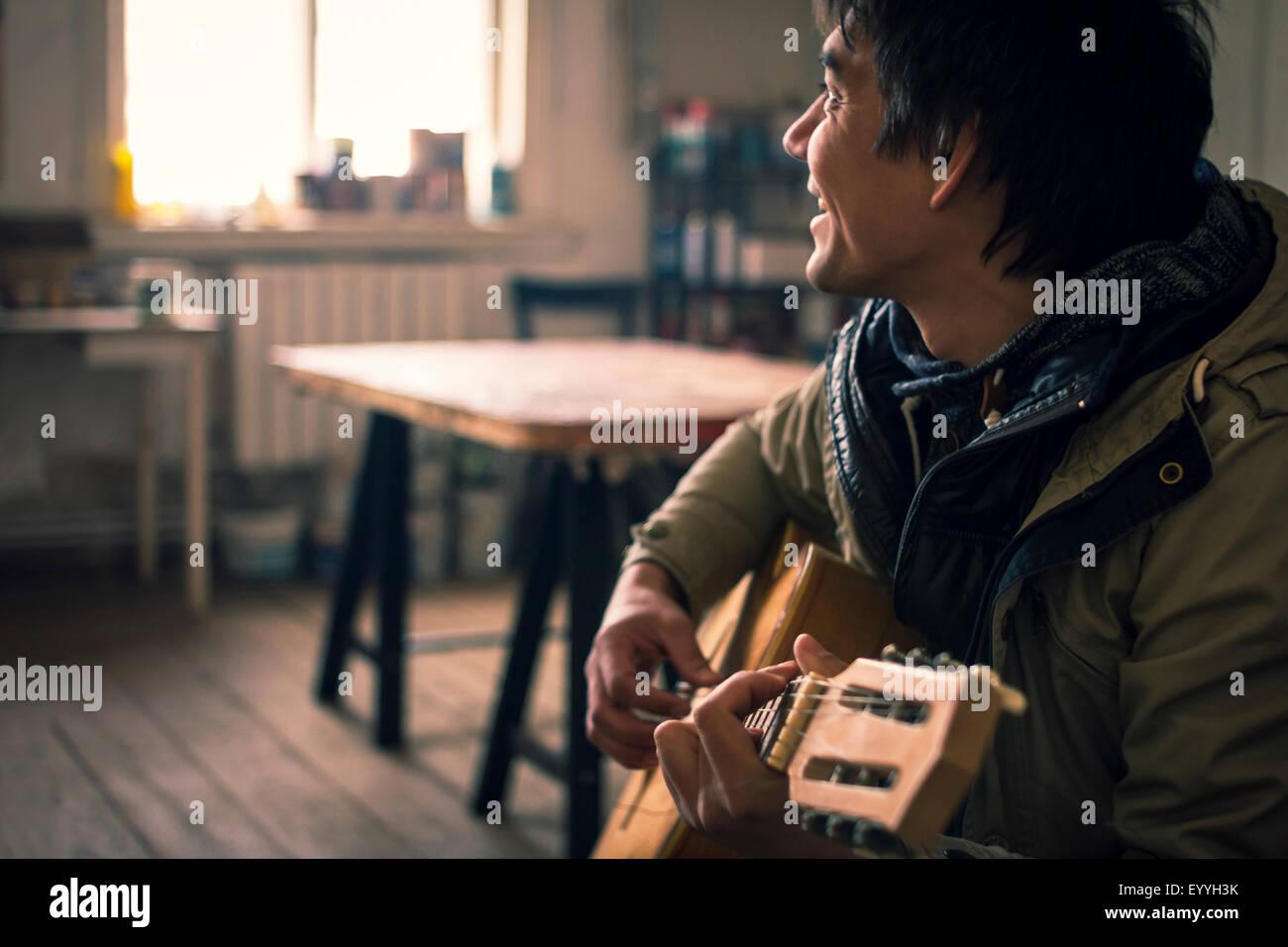 Asiatischer Mann Gitarre spielen im Innenbereich Stockfoto