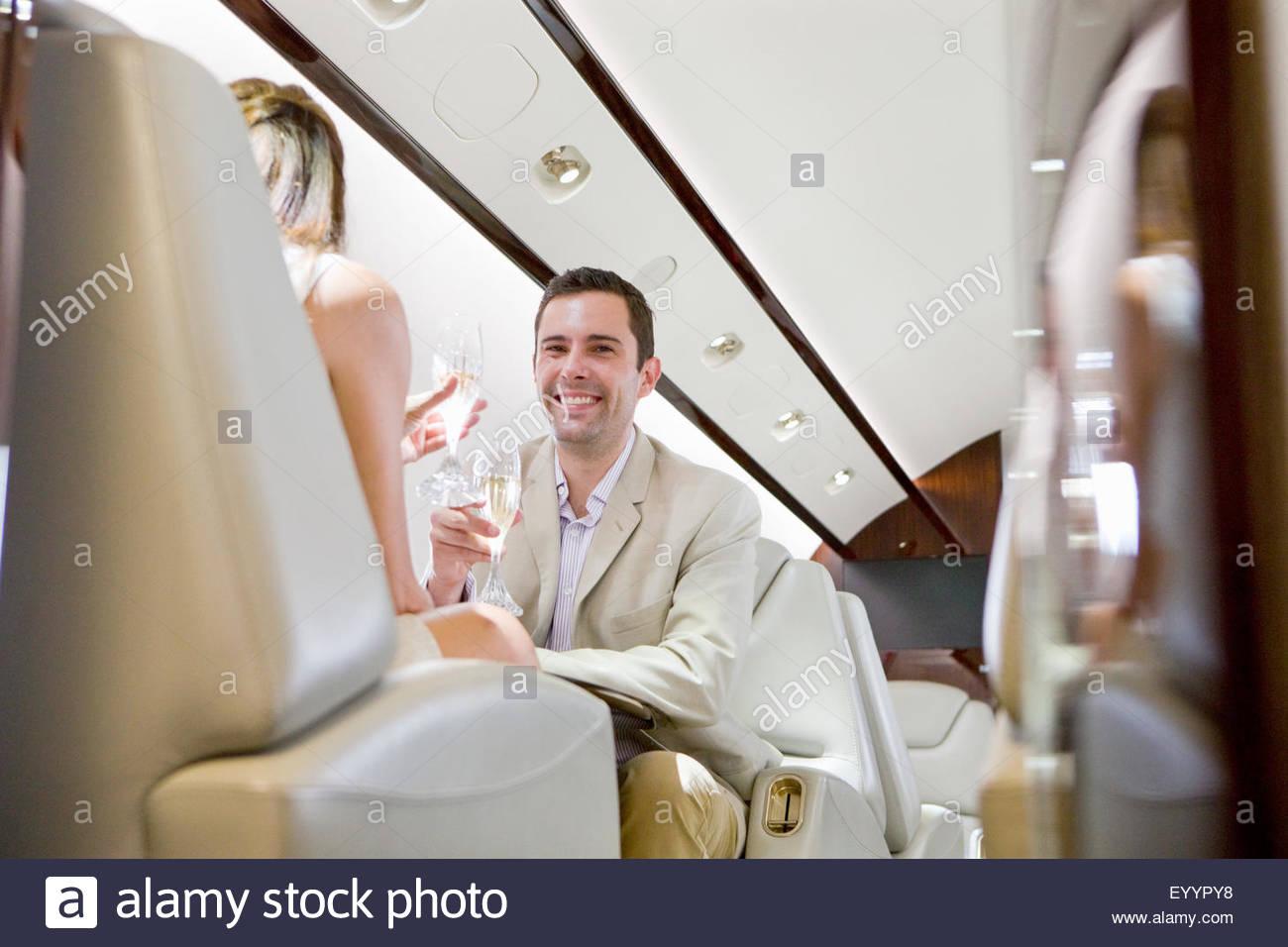 Attraktives Lächeln paar trinken Champagner auf privat-jet Stockbild