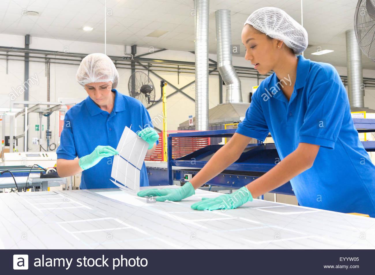 Techniker, die Vermittlung von Solarzellen auf Form-Solar-Panel im Produktionsbereich Stockbild