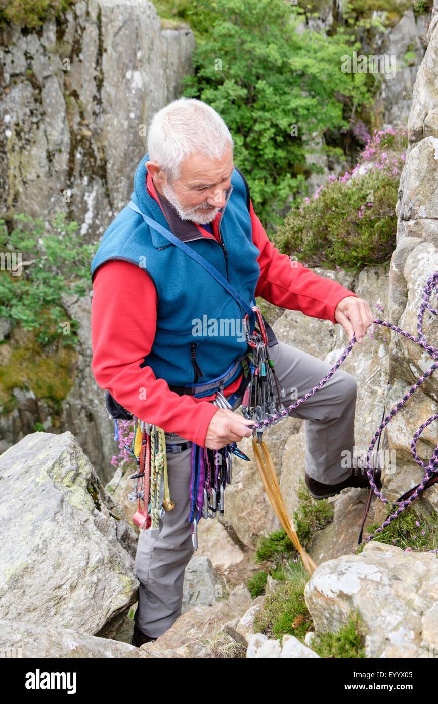 Erfahrene aktive Senioren senior rockclimber Absicherbare oben auf einem Felsen Klettern im Freien. North Wales, Stockbild