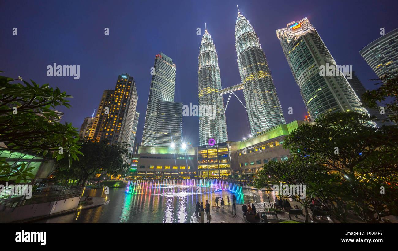 Wasser-Brunnen im Suria KLCC mit Petronas Towers und Bürogebäuden bei Sonnenuntergang blaue Stunde in Stockbild