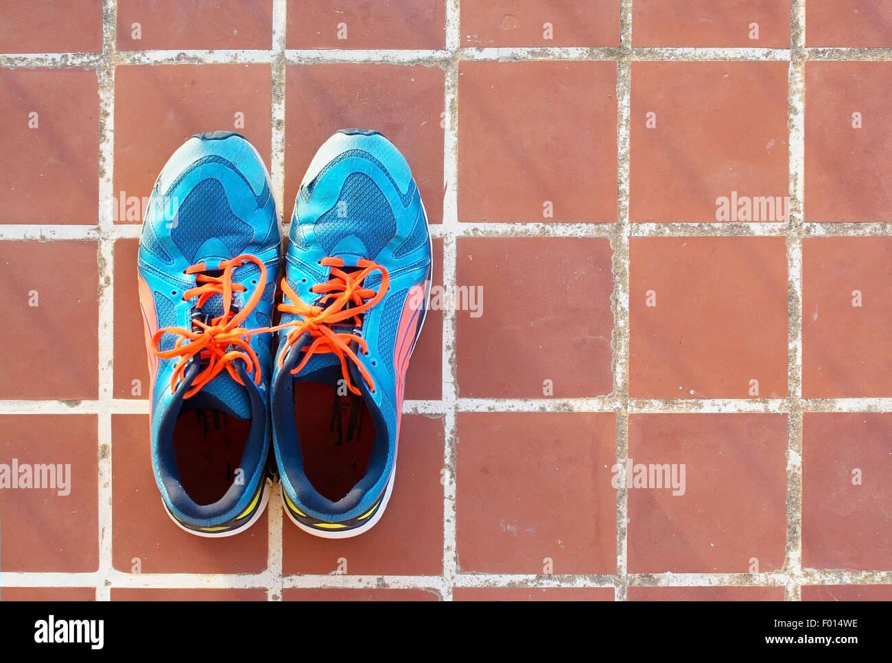 Blaue Sportschuhe auf Terrakotta Boden Platz Fliesen Hintergrundtextur. Stockbild