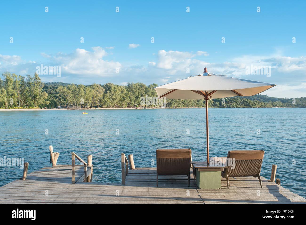 Sommer, Reisen, Urlaub und Ferien-Konzept - Liegestühle und Sonnenschirm am Schreibtisch aus Holz gegen blauen Stockbild