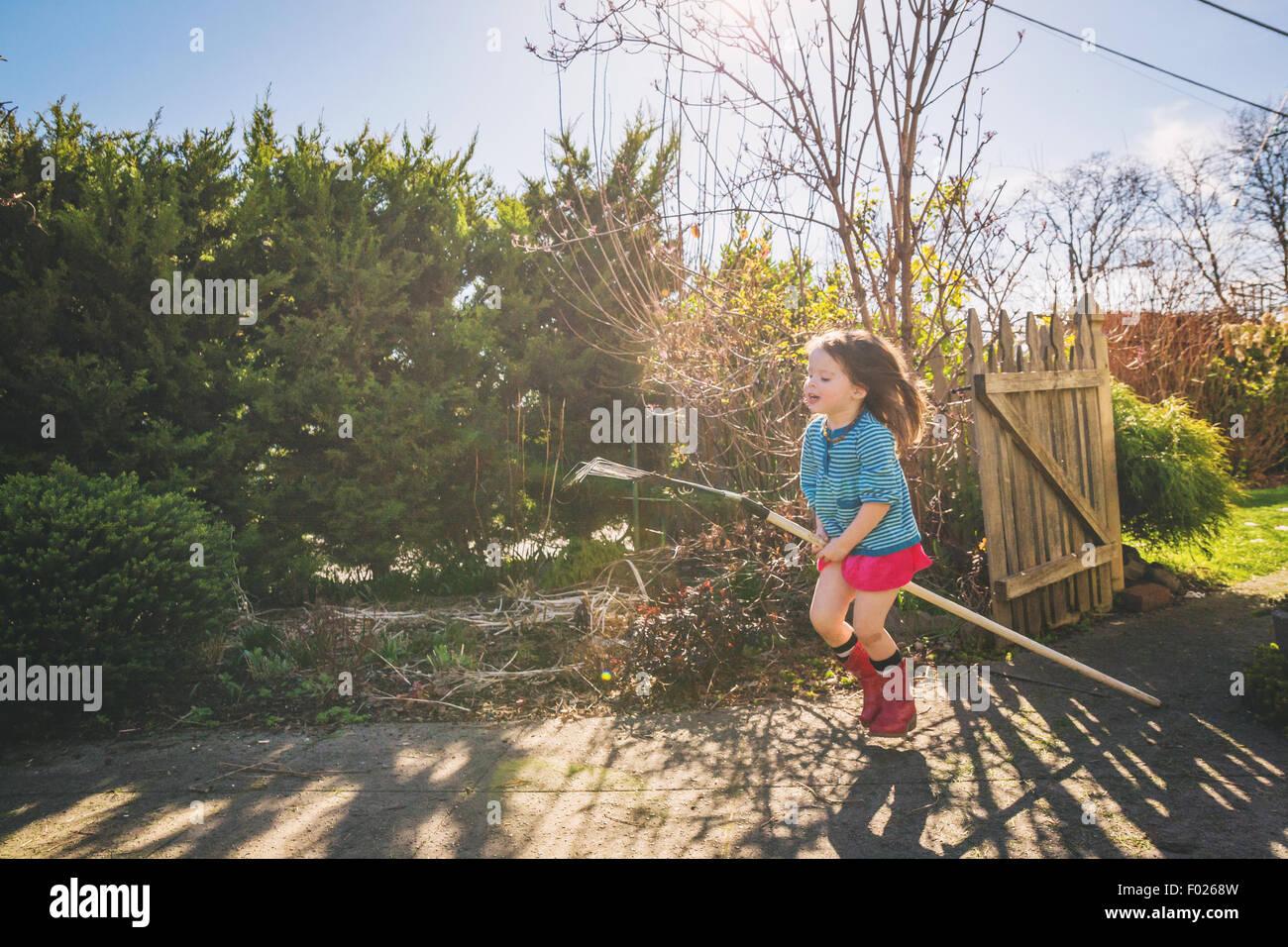 Junges Mädchen reiten Rechen durch Hof, wie es ist ein Pferd Stockbild