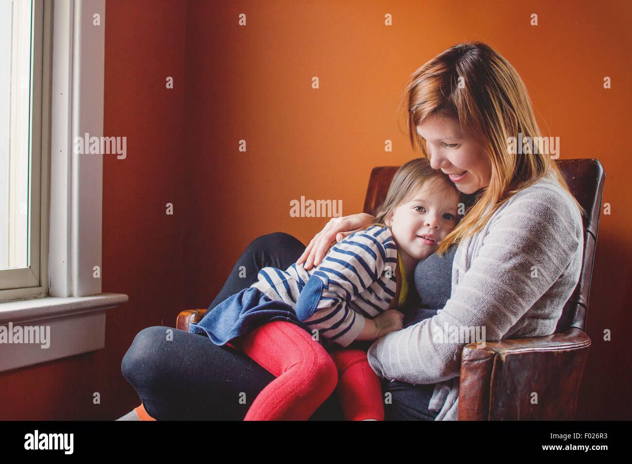Mutter und Tochter zusammen in einem Sessel sitzend Stockbild