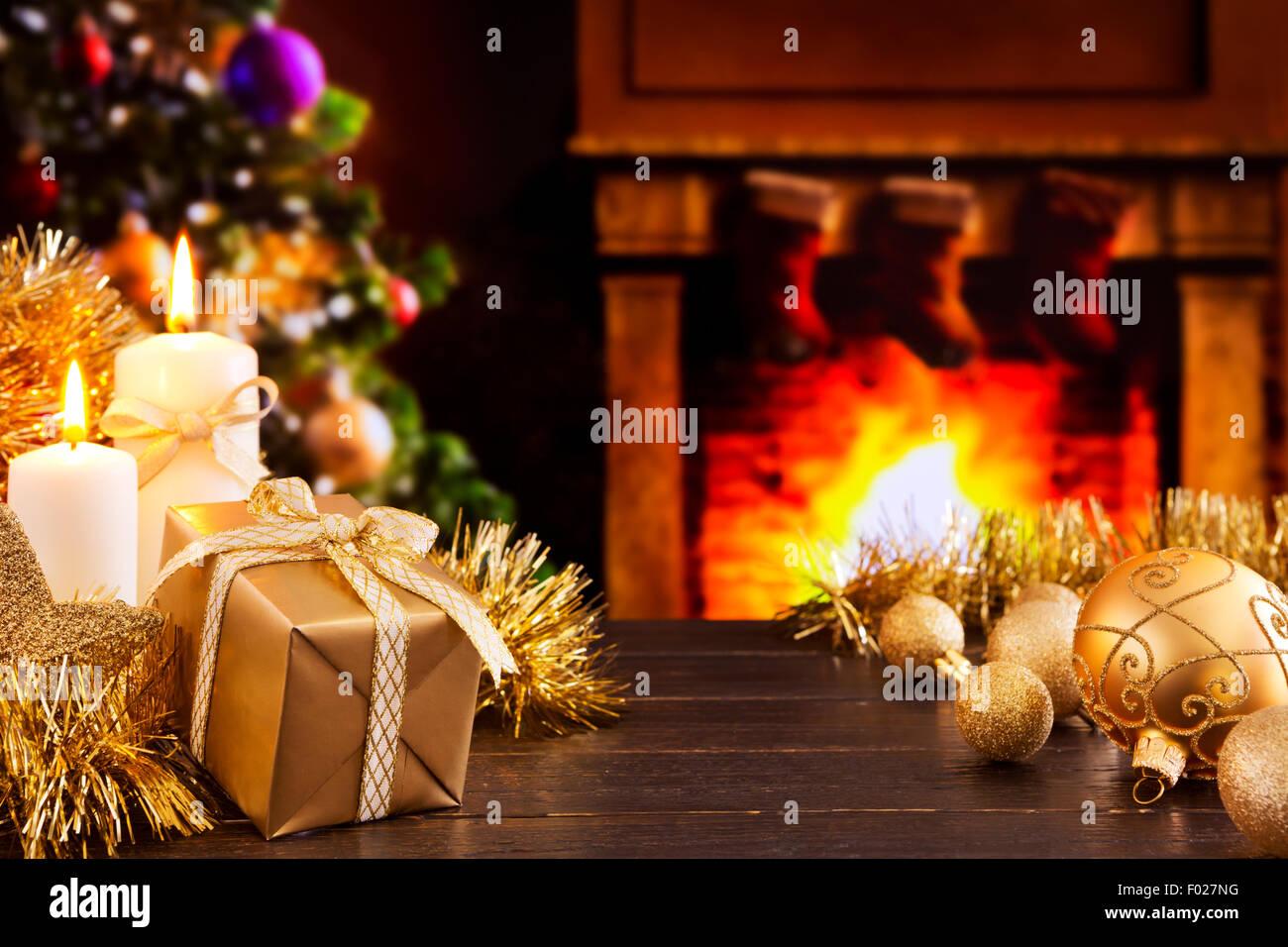 Ein Geschenk, Weihnachtsschmuck und Kerzen vor der Kamin. Im Kamin brennt ein Feuer. Stockbild