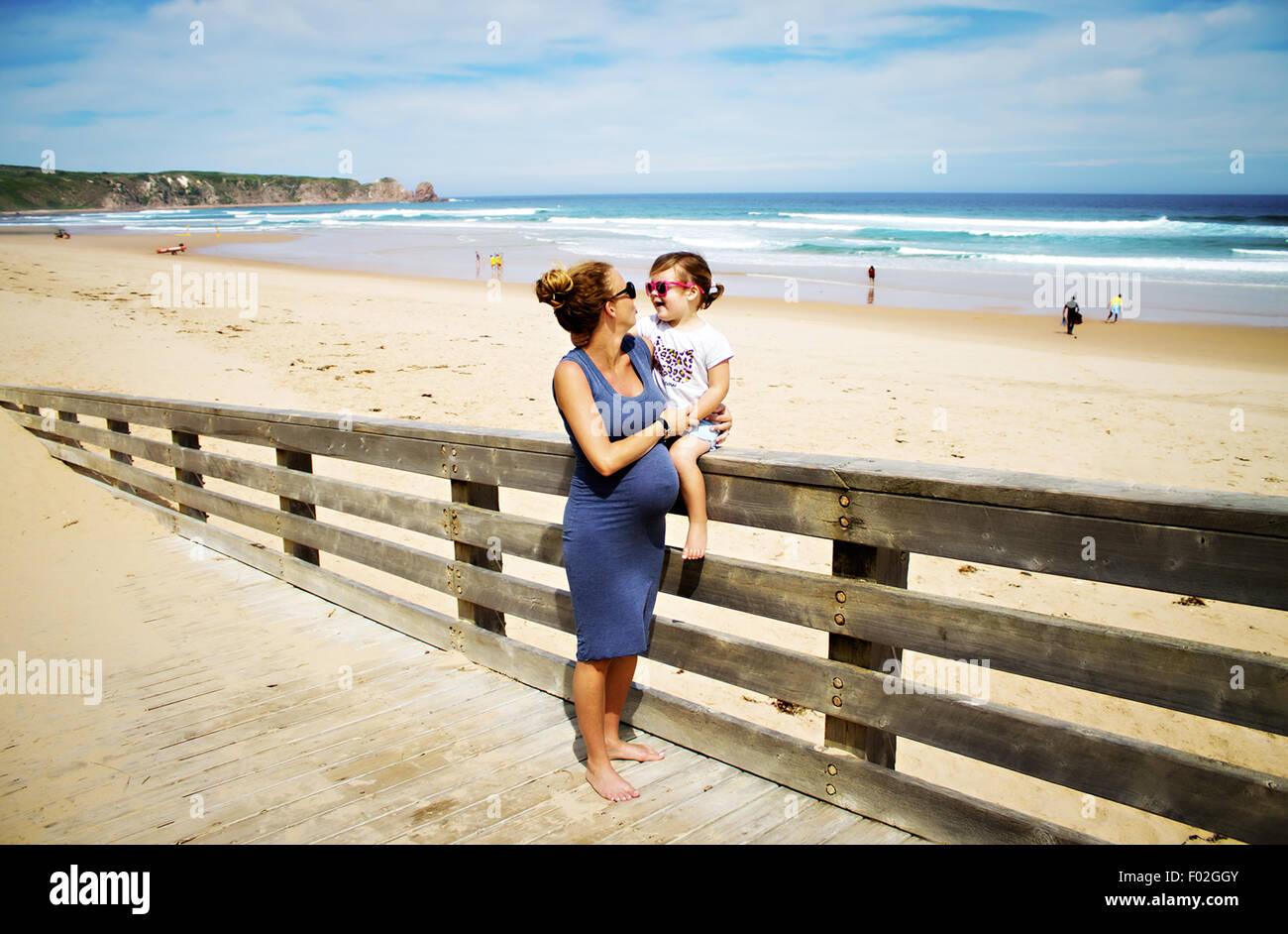 Schwangere Frau am Strand mit ihrer Tochter Stockbild