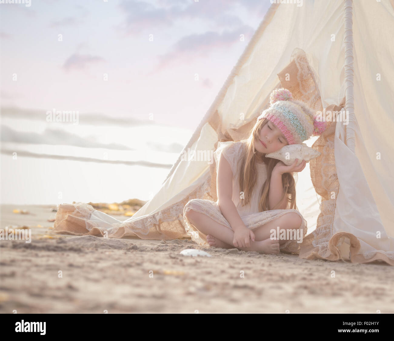 Mädchen sitzen in einem Wigwam am Strand anhören einer Muschel Stockbild