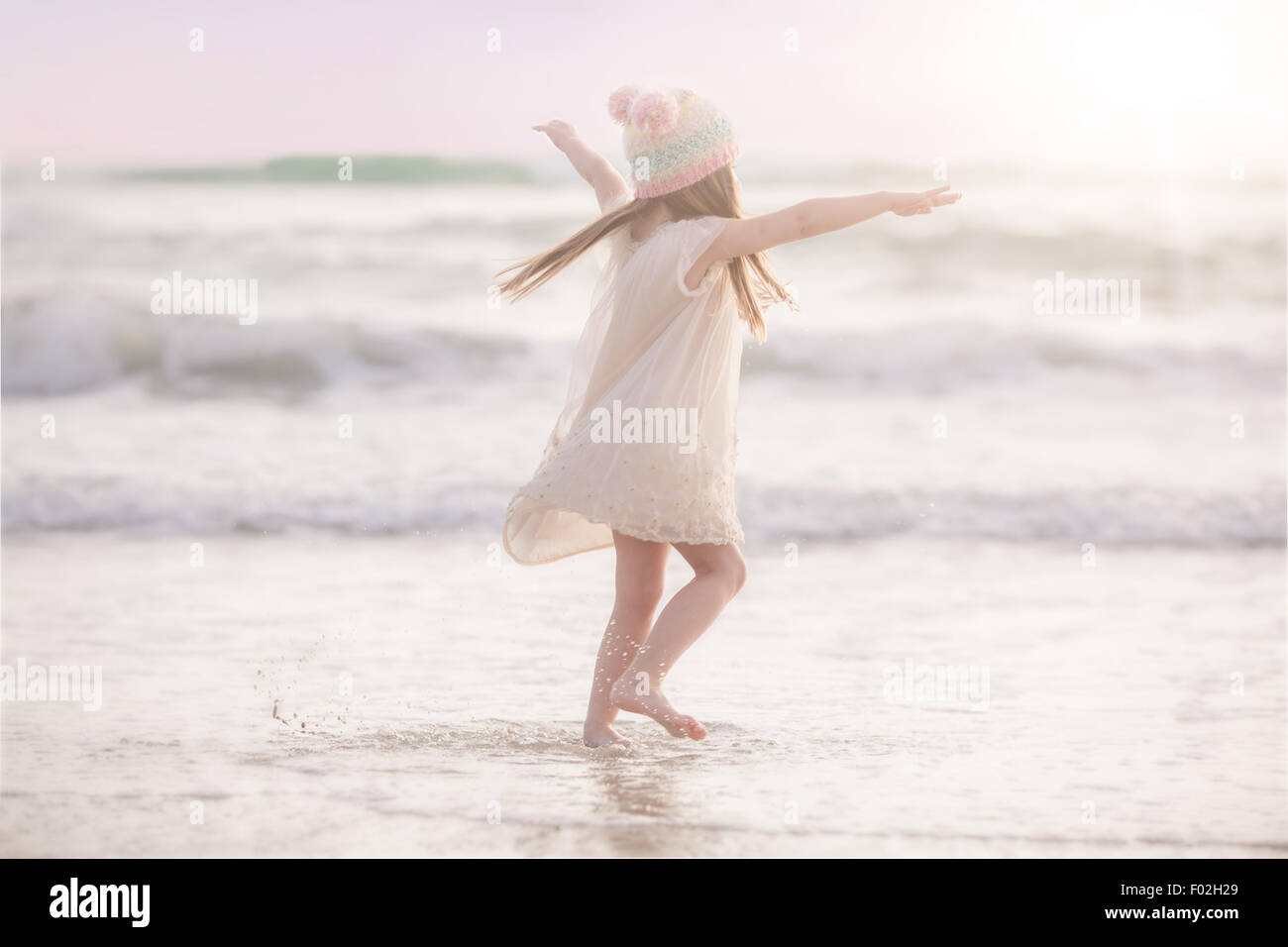 Mädchen tanzen am Strand Stockbild