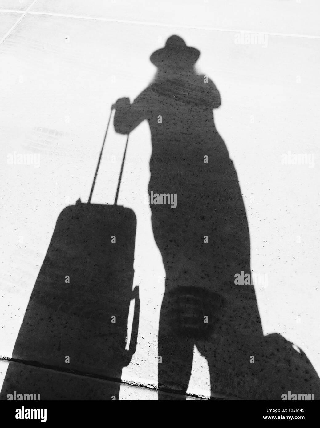 Schatten einer Frau mit einem Koffer Stockbild