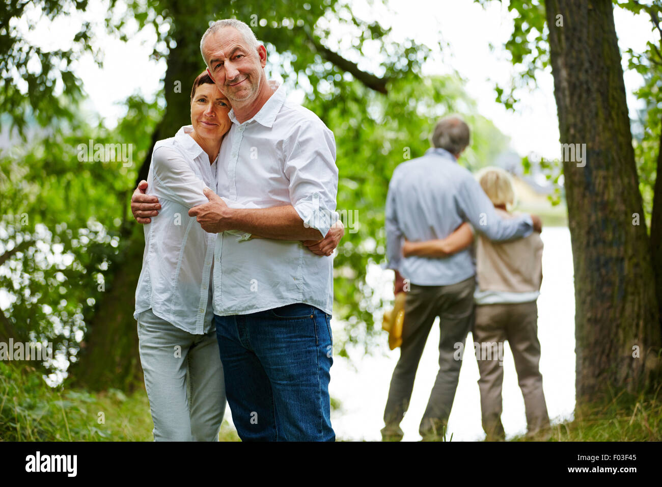 Zwei glückliche ältere Ehepaare, die im Garten des Altersheim umarmen Stockbild