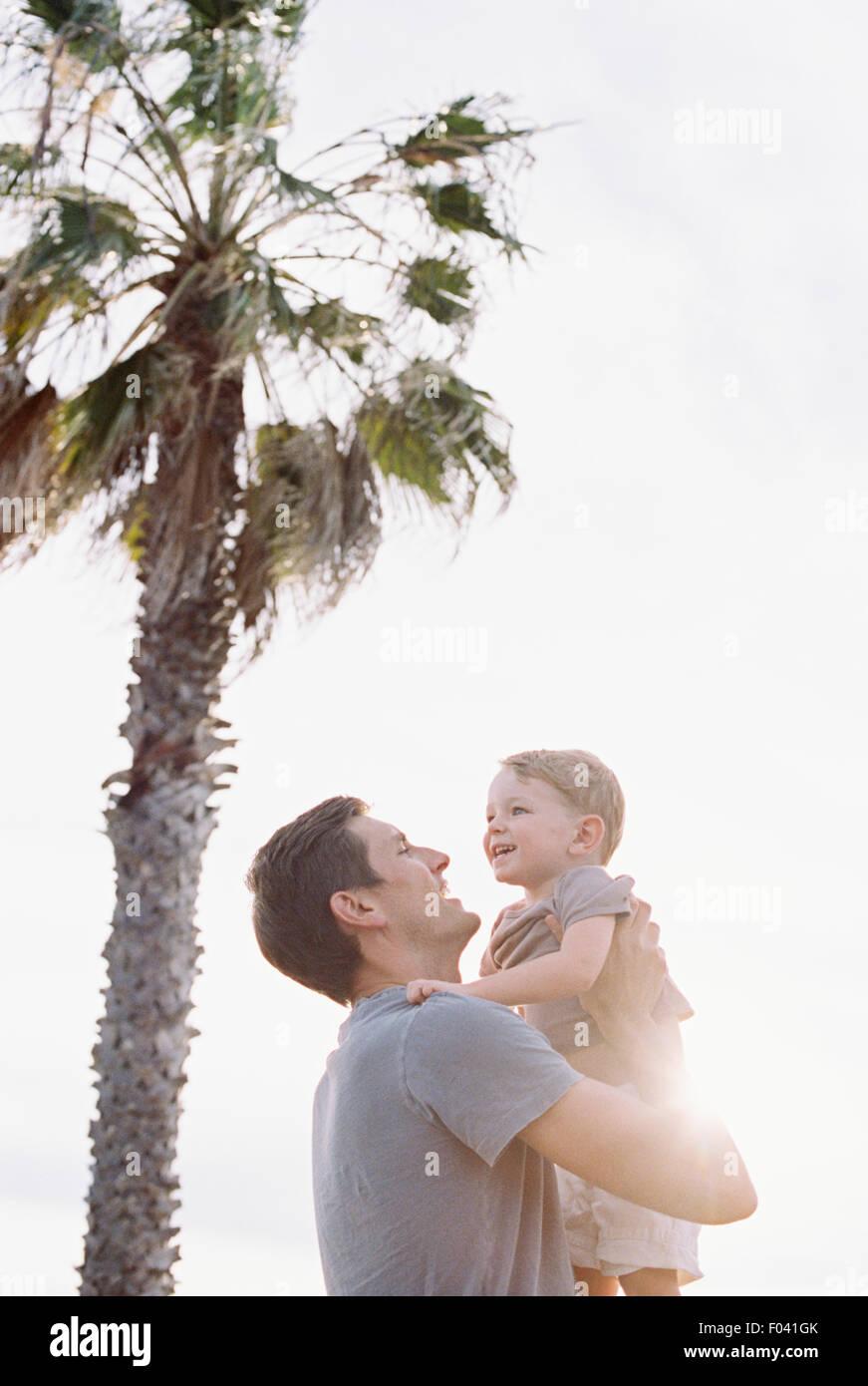 Lächelnder Mann von einer Palme stehend, seinen kleinen Sohn auf dem Arm tragen. Stockbild