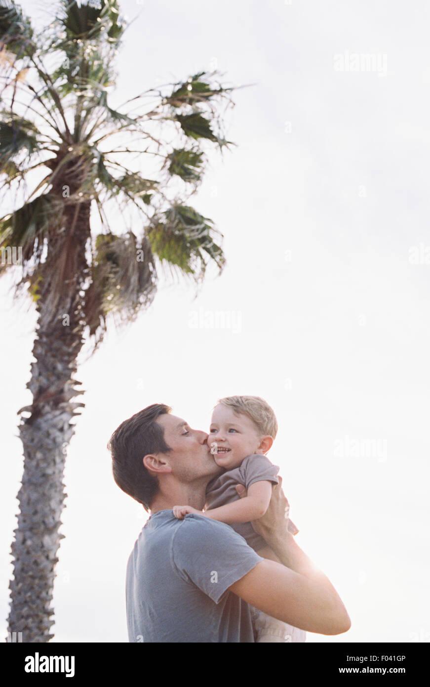 Mann von einer Palme stehend, seinen kleinen Sohn auf dem Arm tragen, ihn auf die Wange zu küssen. Stockbild