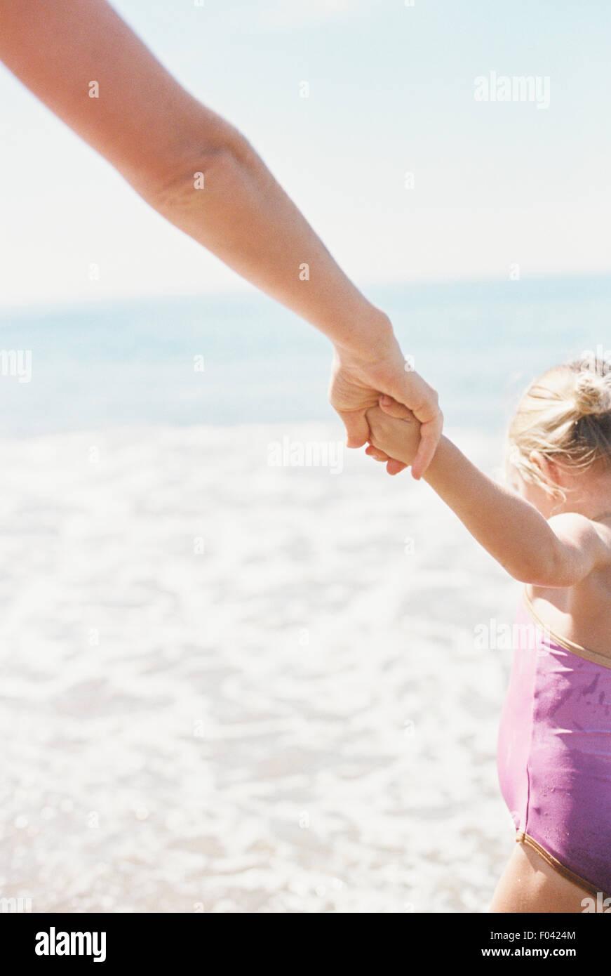 Frau und ihre Tochter Hand in Hand, stehend auf einem sandigen Strand von He-Meer. Stockbild