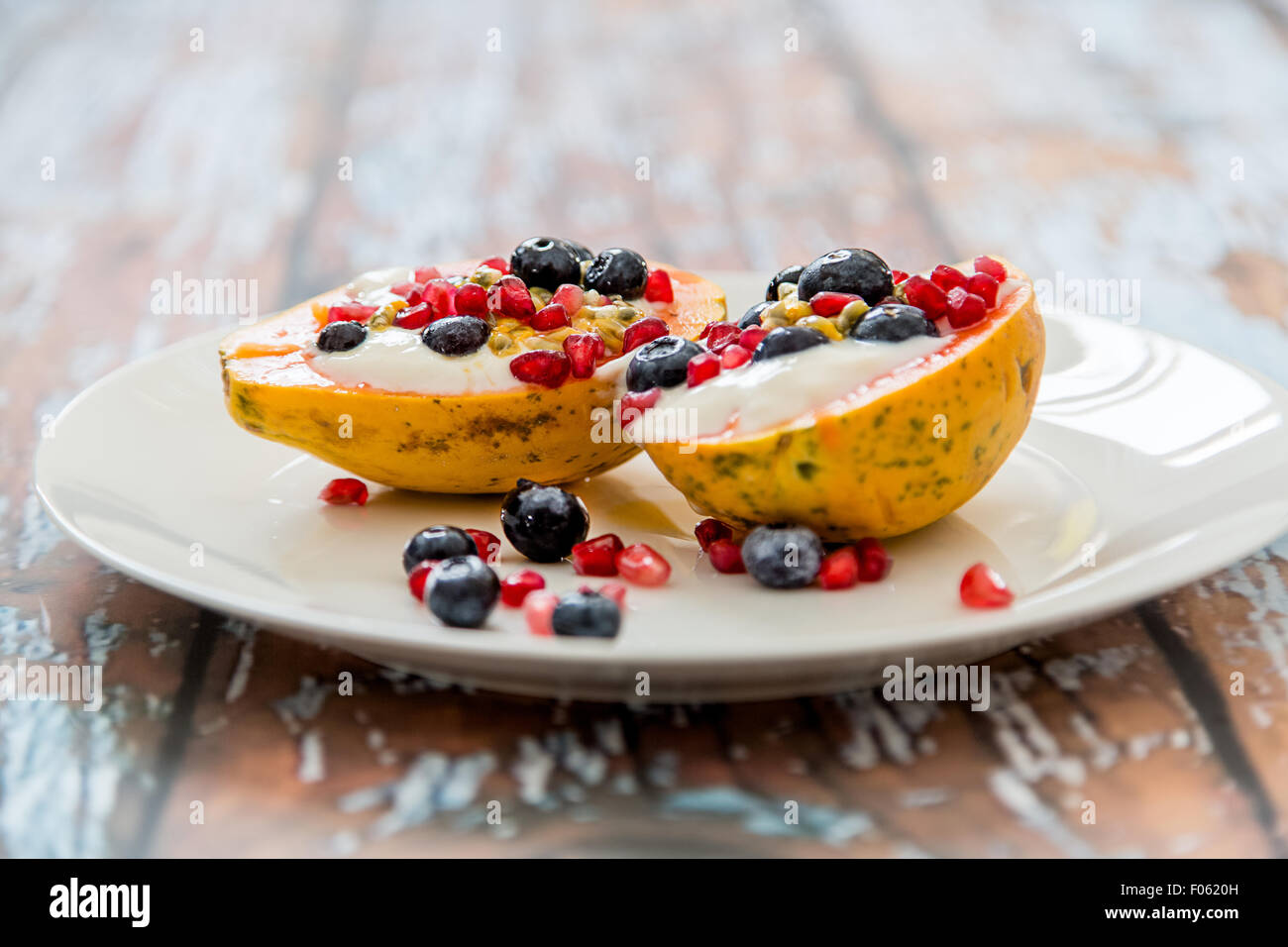 Papaya mit natürliche Soja-Joghurt und frischen Beeren, leichtes und gesundes Frühstück, Papaya, Heidelbeeren, Passionsfrucht, Stockfoto