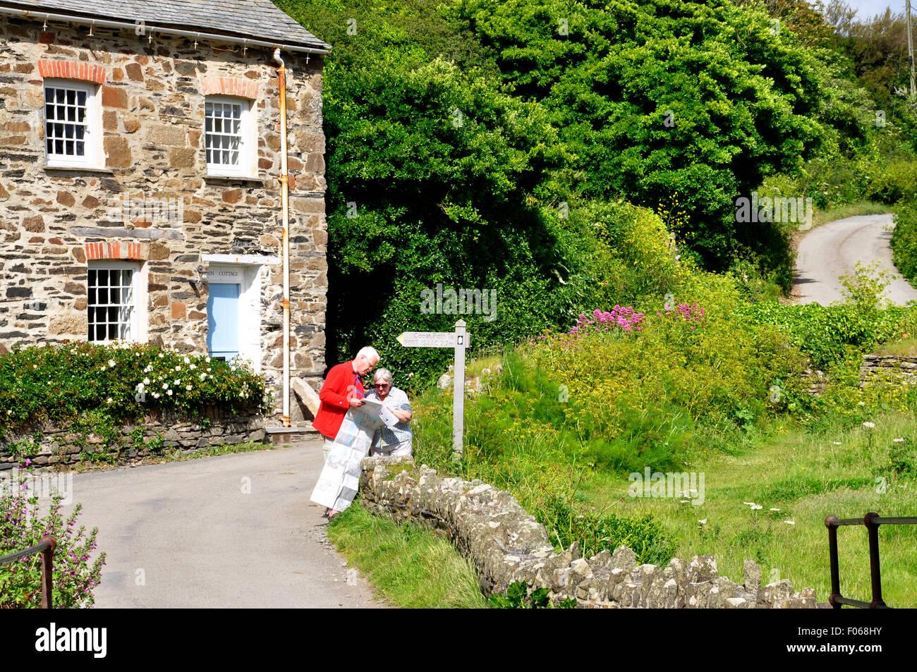 N-te Cornwall - Wicklung Country Lane - Finger Post - paar Blick auf eine Karte - Ferienhaus in der Nähe von Stockbild