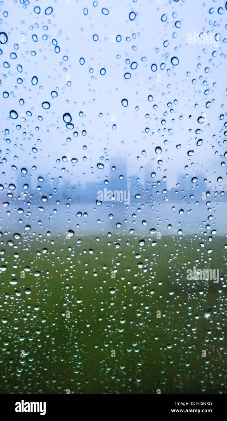 Tröpfchen Regen auf ein Fenster mit der Silhouette einer Stadt im Hintergrund. Stockbild