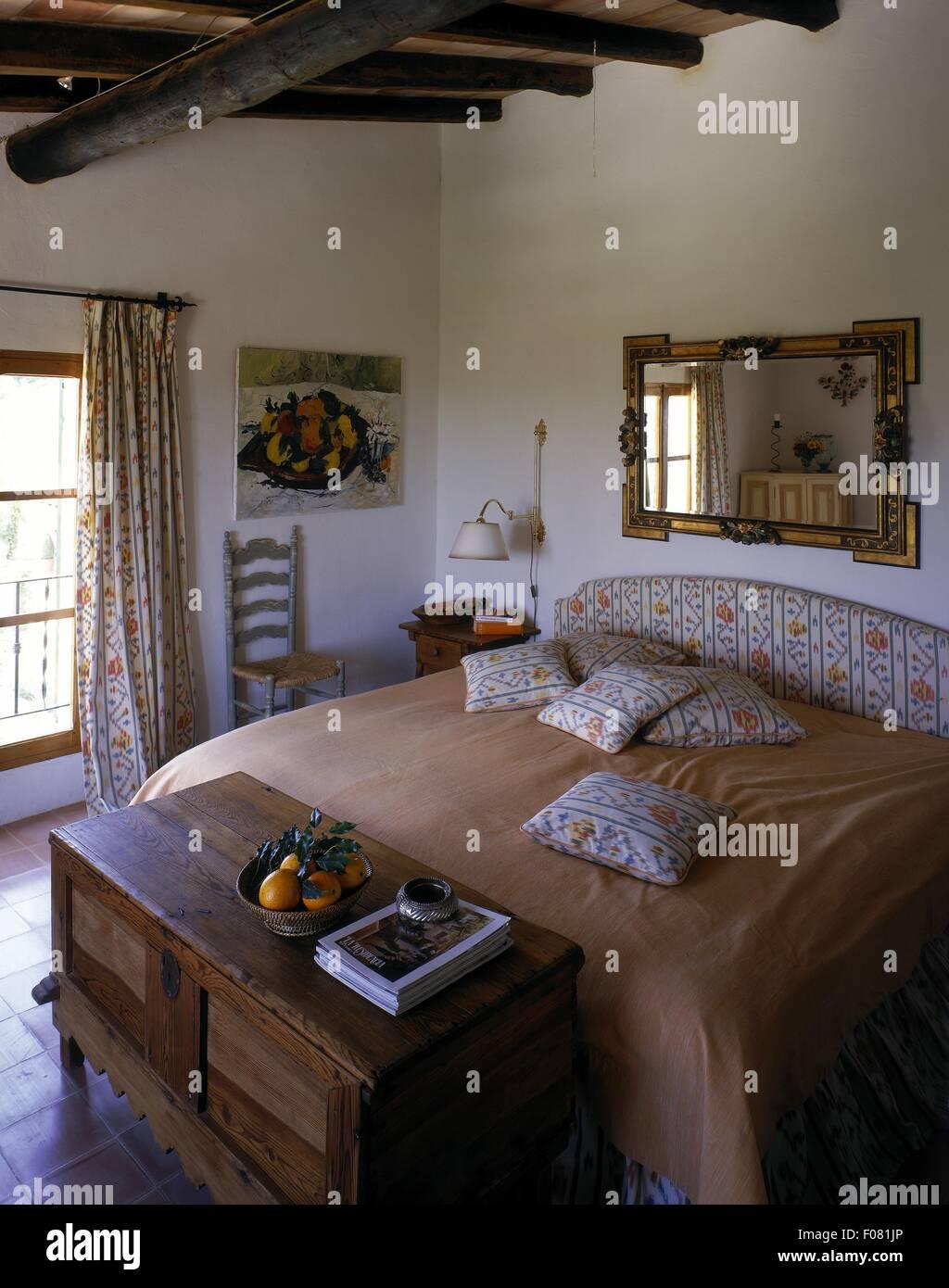 Rustikale Schlafzimmer mit Balkendecke, Holzkiste und Fliesen ...