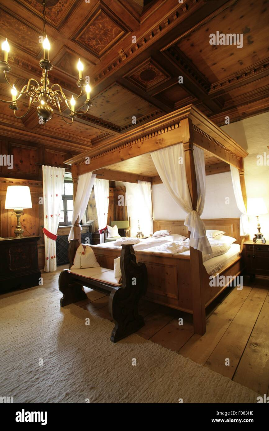 Schlafzimmer mit Himmelbett aus Holz und Kronleuchter in Hotel ...