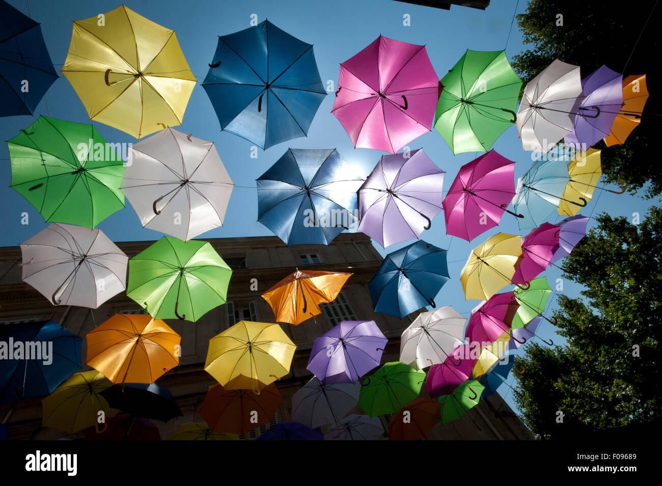 Hell farbige Sonnenschirme schwimmende füllen den Himmel über Rue Jean Jaurès, Arles, Departement Stockbild