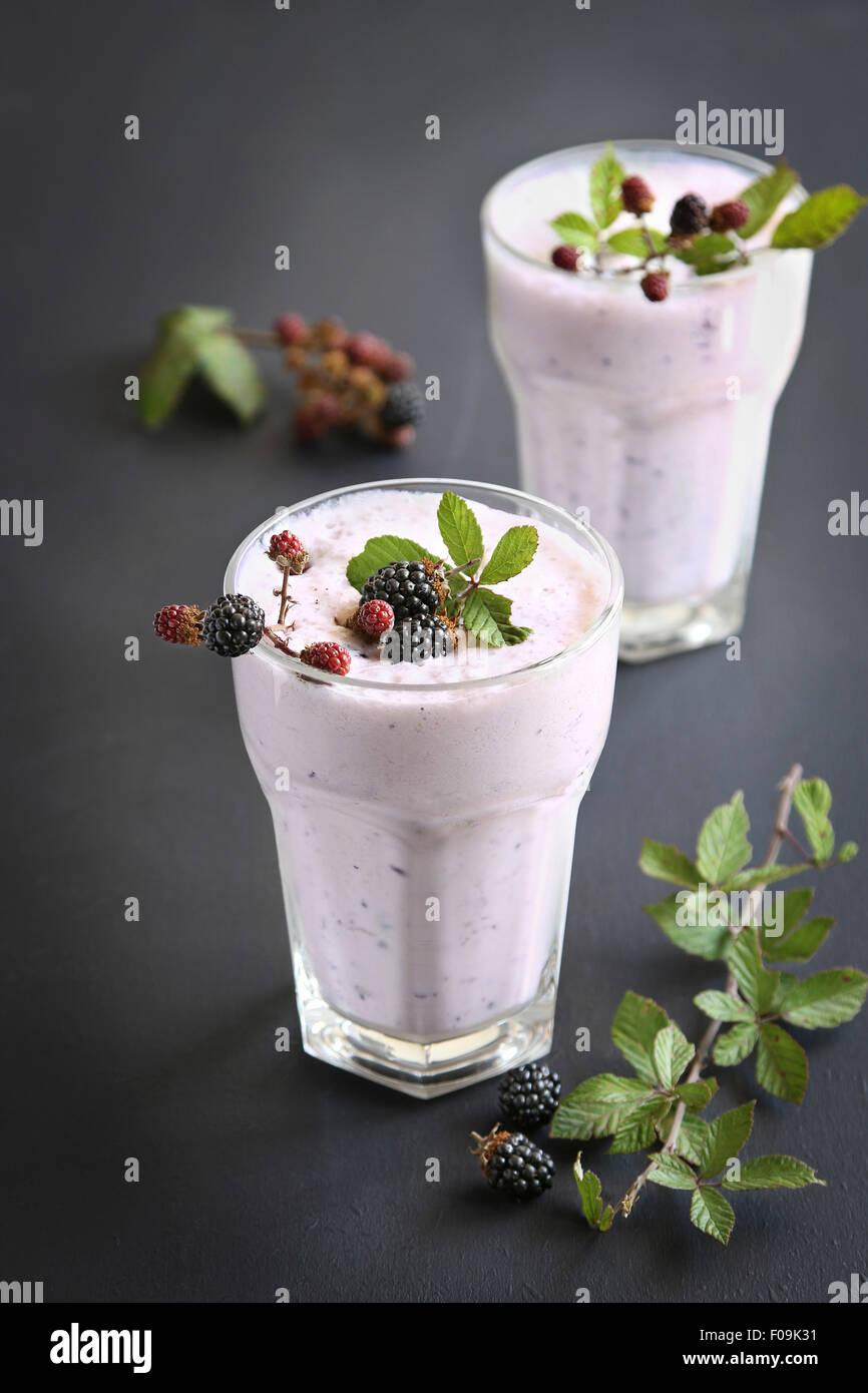 Zwei Gläser mit Blackberry-Smoothie, dekoriert mit frischen Brombeeren Stockbild